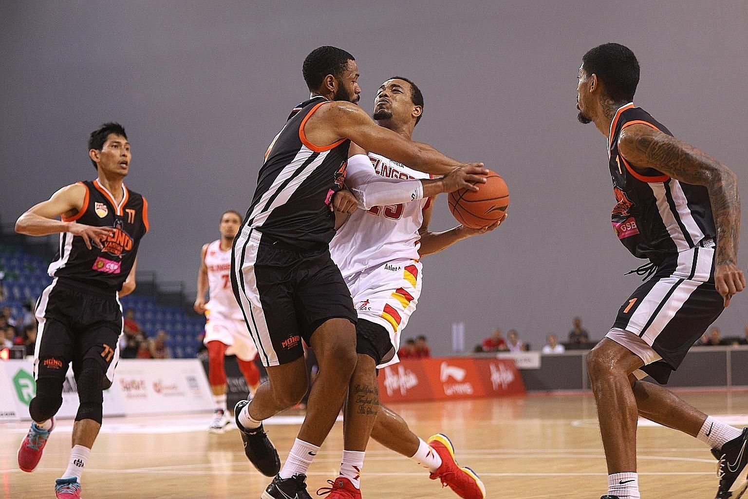 Slingers forward Xavier Alexander battling to retain possession during the ABL game against Mono Vampire at OCBC Arena yesterday. He took the final shot of the game and, while his two-pointer fell through the hoop, he did not get it off in time.