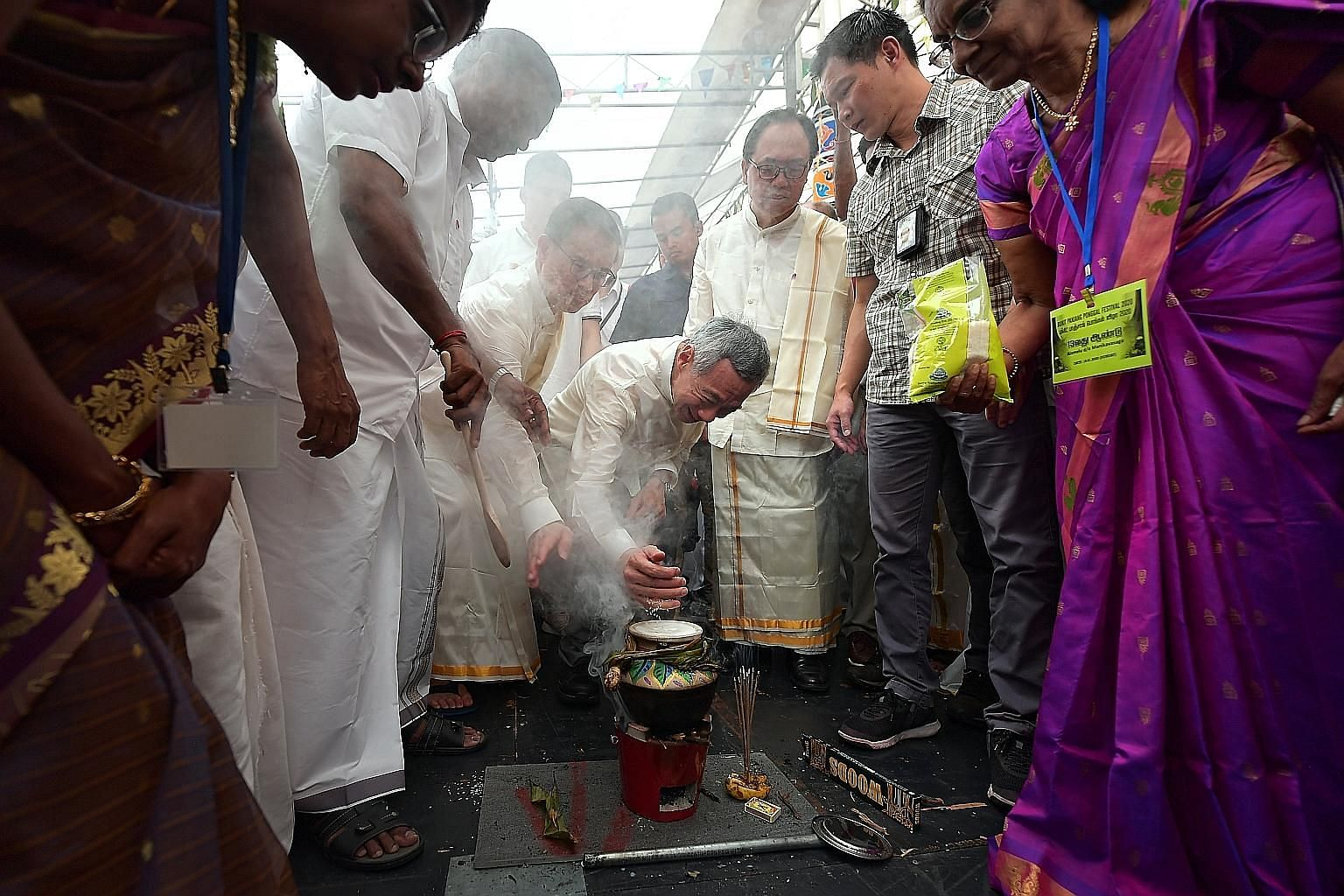 Prime Minister Lee Hsien Loong adding rice grains to a pot of boiling milk yesterday. During Pongal, cooking rice in fresh milk until the mix overflows from the pot symbolises abundance and fortune. The festivities were hosted by Bukit Panjang MP Teo