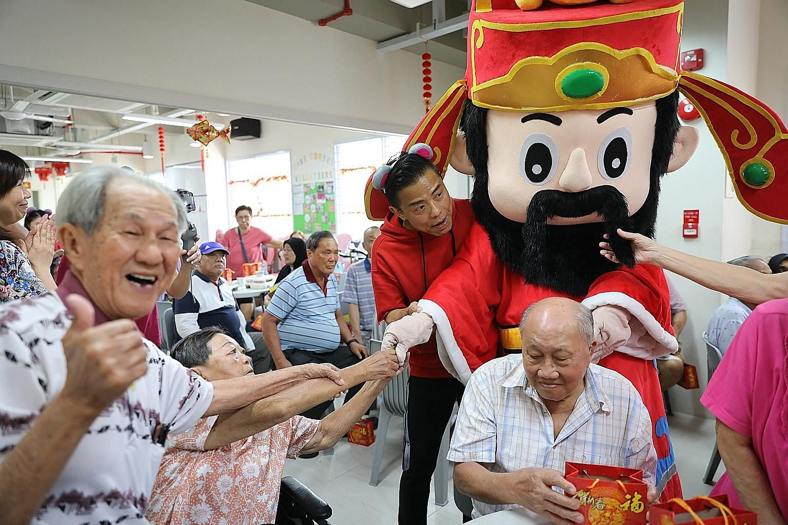 Mr Teo Kiong Chiang (left), 81, a senior at Care Corner Senior Activity Centre, gives the thumbs up as the God of Fortune distributes oranges to the elderly. The man dressed as the God of Fortune is 48-year-old Andrew Lum, SPH's assistant manager of