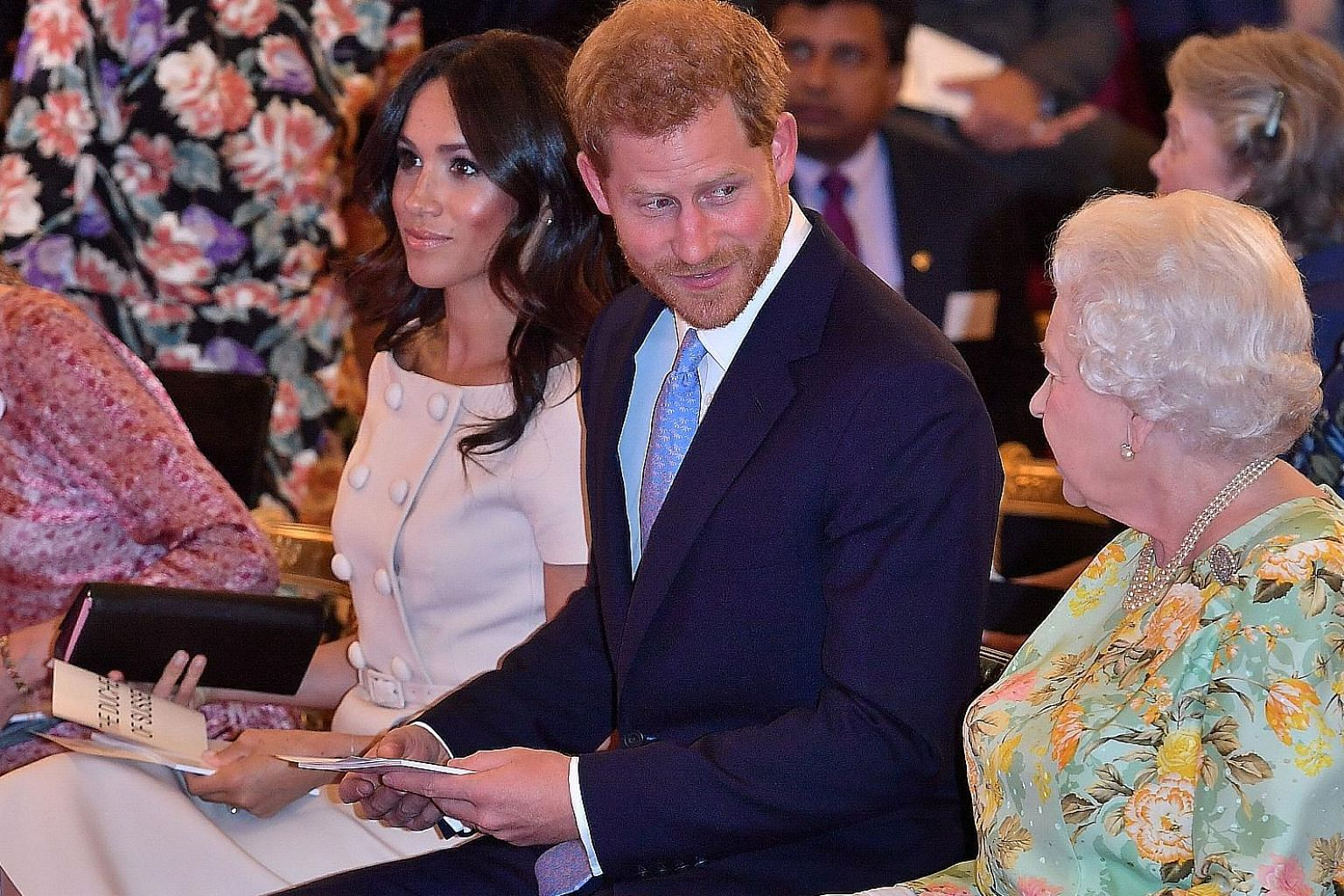 A 2018 photo of Britain's Queen Elizabeth with Prince Harry and his wife Meghan at a Buckingham Palace reception.
