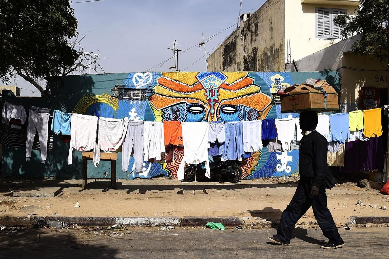 Wet laundry dry in the sun alongside colourful wall murals in Dakar's working-class Medina neighbourhood.