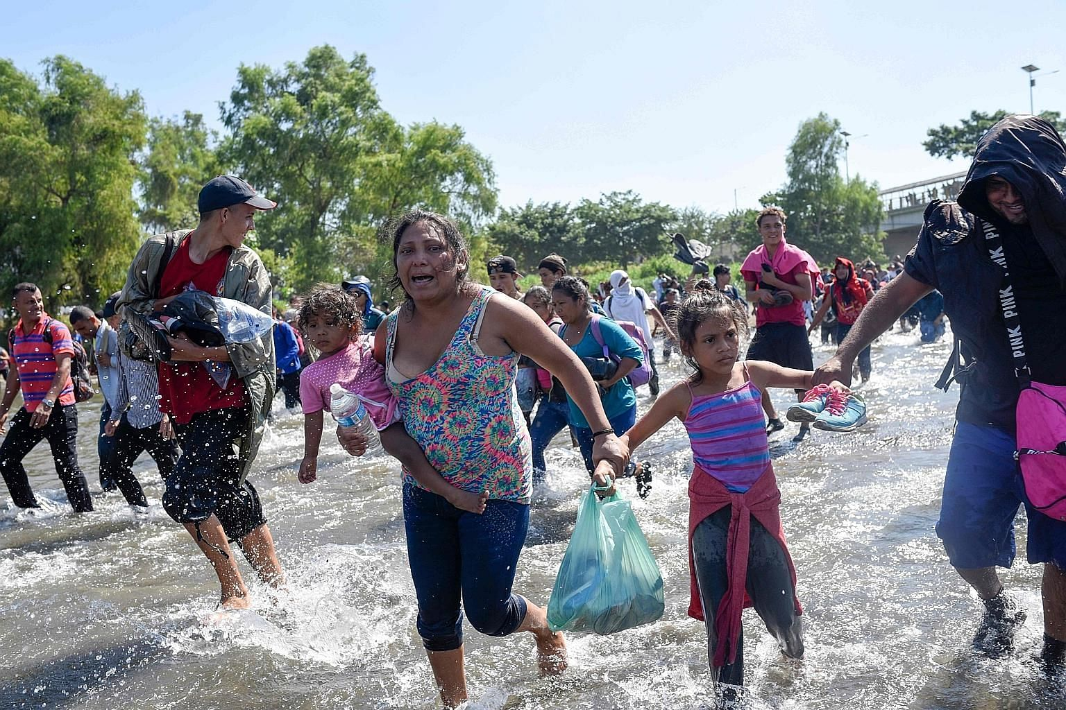 Central American migrants - mostly Hondurans - crossing the Suchiate River between Guatemala and Mexico on Monday. They were part of a group of several thousand people that had left Honduras last week.
