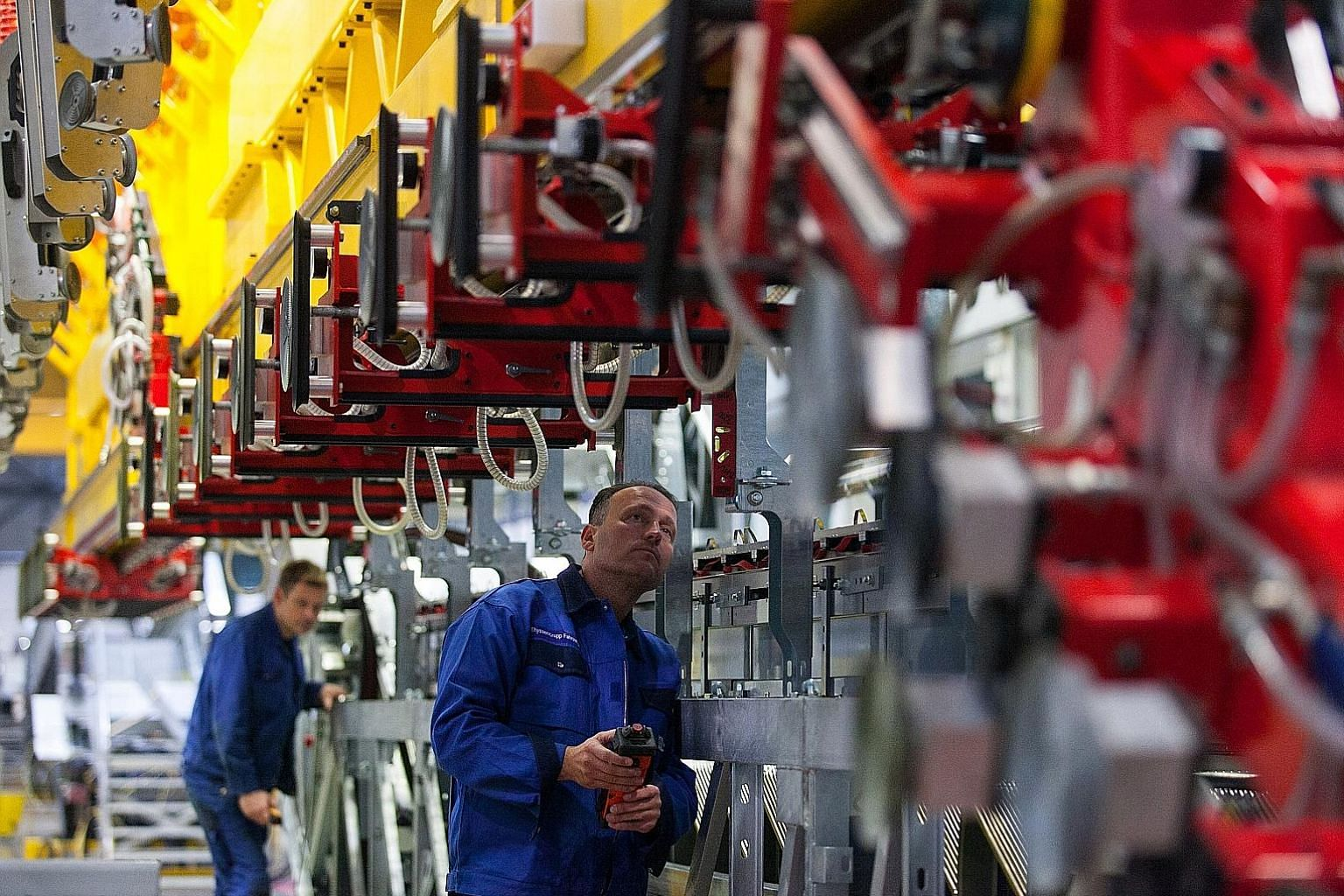 Employees at the Thyssenkrupp factory in Hamburg, Germany, working on assembling escalators. Brookfield Asset Management, which partnered Temasek, is still in the running for the elevator unit, say sources. PHOTO: BLOOMBERG