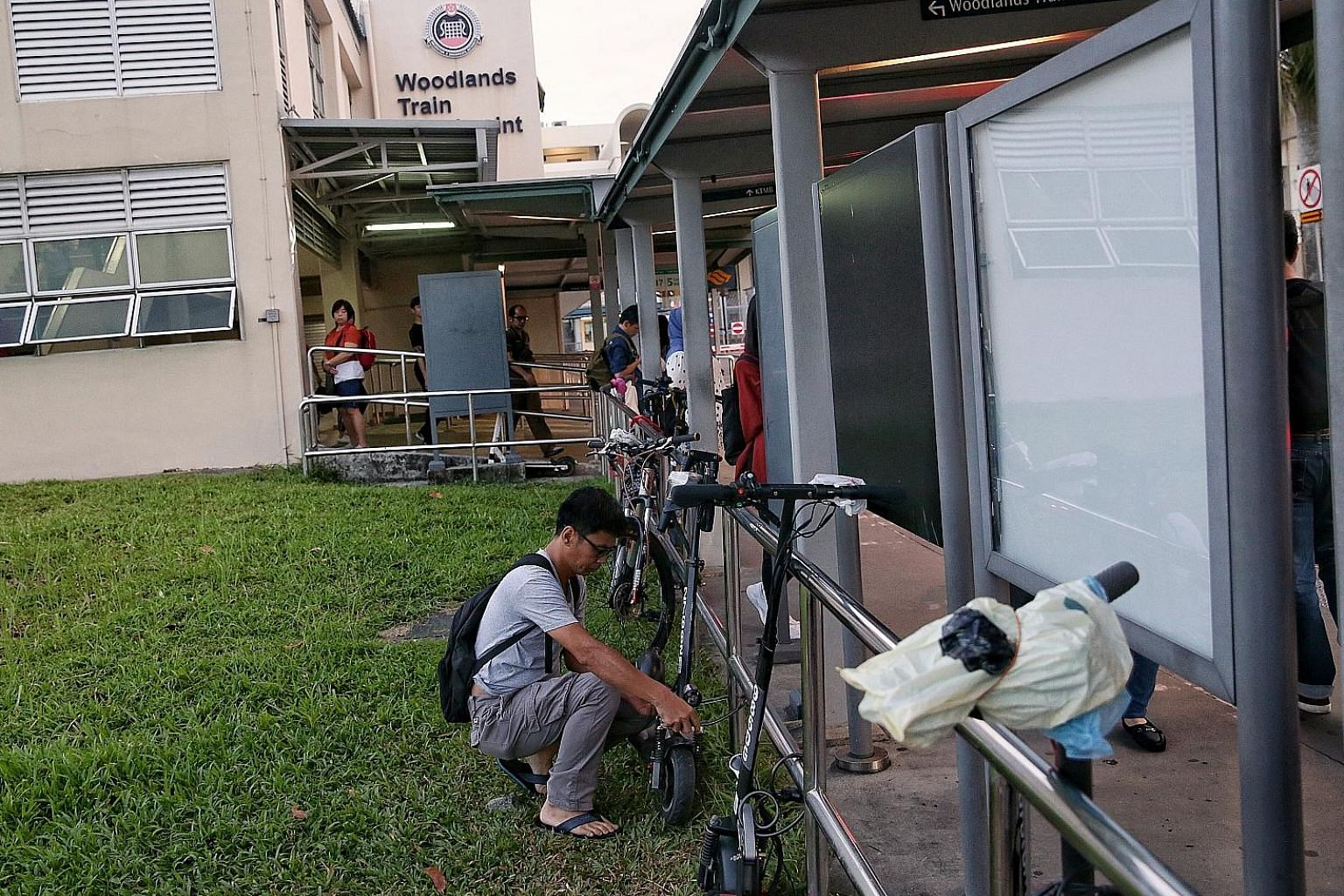 Some Malaysians who commute to work in Singapore are still riding their e-scooters into the Republic (above), but have been parking them near the Woodlands Checkpoint since the devices are banned from footpaths in Singapore. A number of workers lock