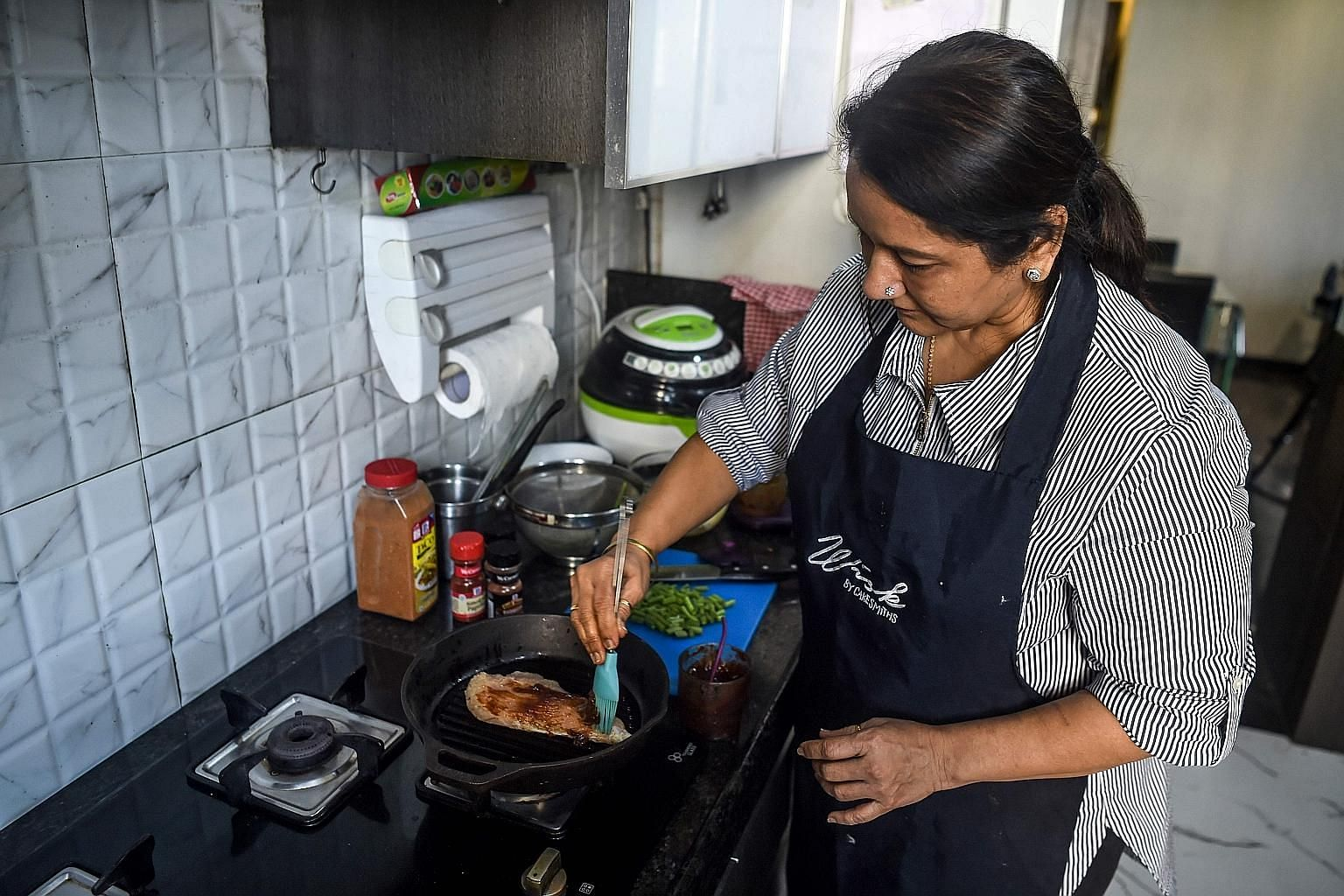 Madam Rashmi Sahijwala preparing a dish in her kitchen in Mumbai. New apps like Curryful, Homefoodi and Nanighar are giving Indian housewives - many of whom have long struggled to convince conservative families to let them leave home - an opportunity