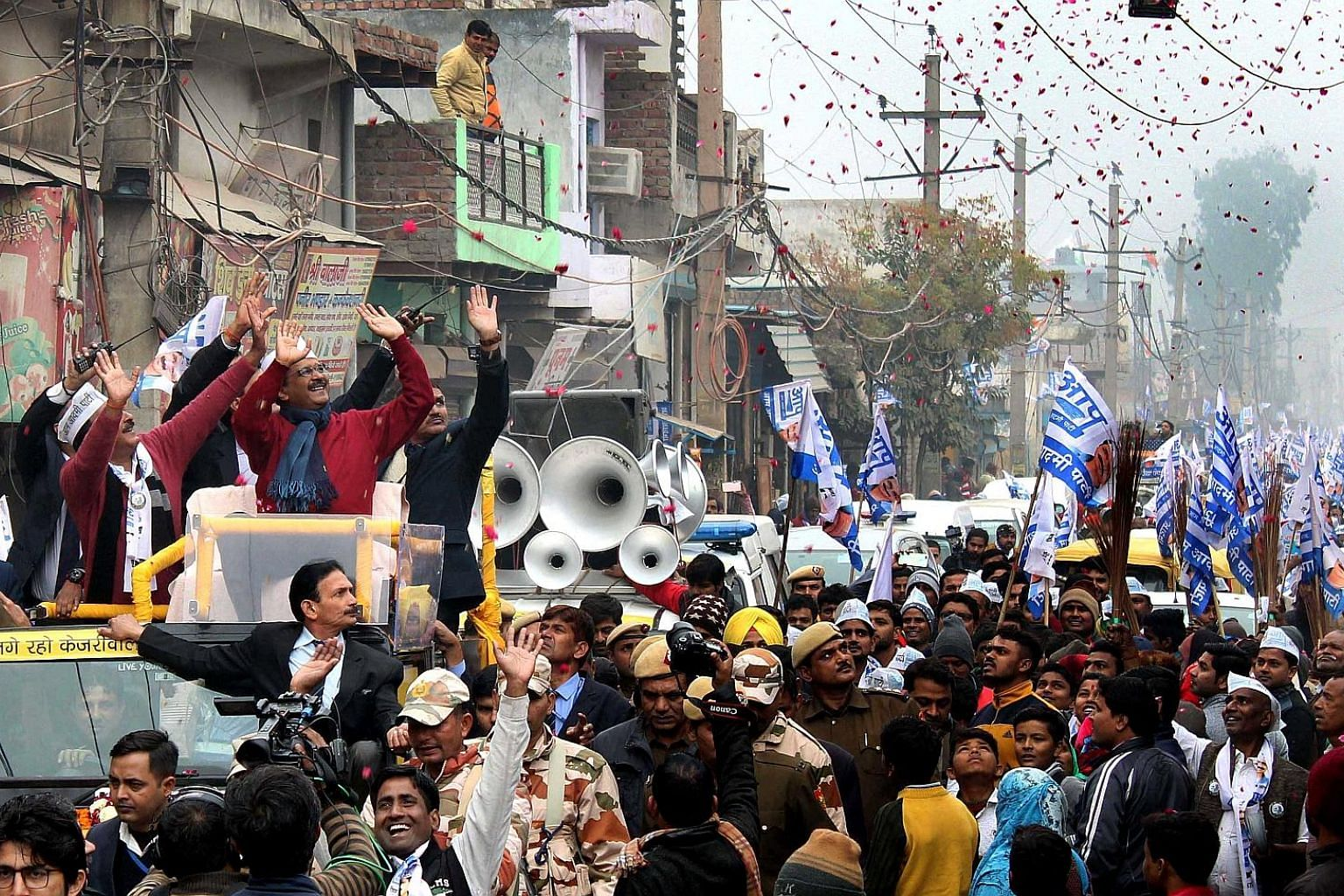 Aam Aadmi Party (AAP) leader and Delhi Chief Minister Arvind Kejriwal (in red sweater and blue scarf) greeting supporters during a roadshow on Wednesday in New Delhi for the upcoming elections. The polls will pit the Bharatiya Janata Party against th