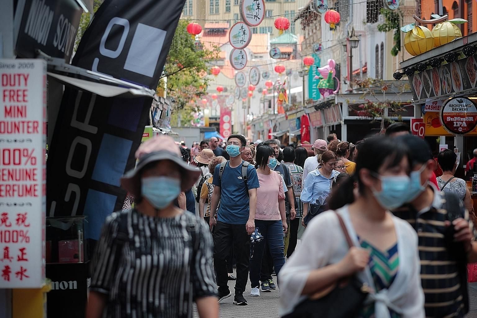 Mask-clad shoppers at Chinatown (above) on the eve of Chinese New Year, and visitors arriving at VivoCity (right) from Sentosa island via the Sentosa Express yesterday. Event organisers are taking precautionary measures, with health advisory posters