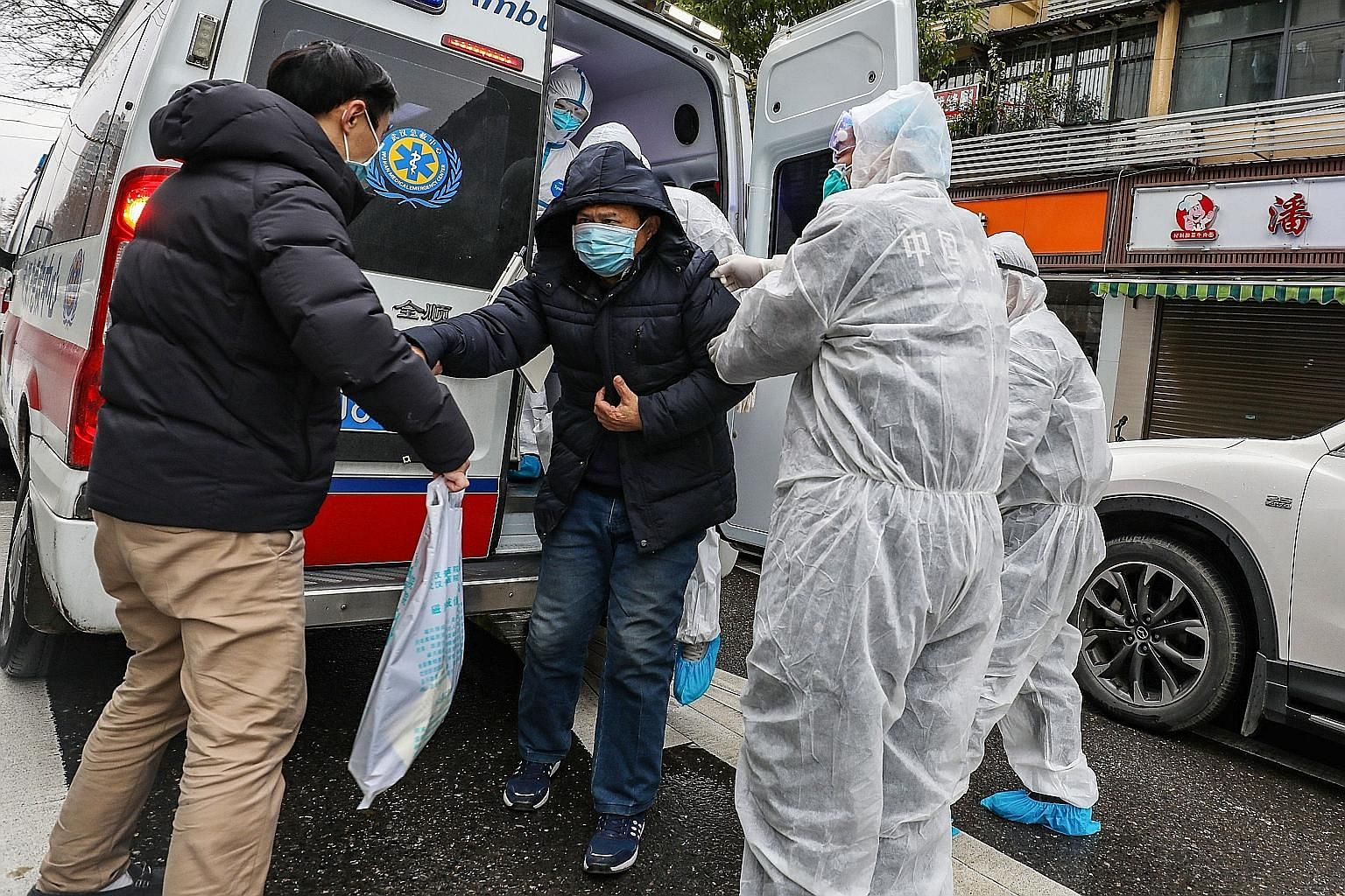 A patient being helped from an ambulance by medical staff at a Hubei hospital. The writer says compared with the Chinese leadership's secrecy and inaction during the Sars epidemic, Chinese President Xi Jinping has responded with speed and alacrity to