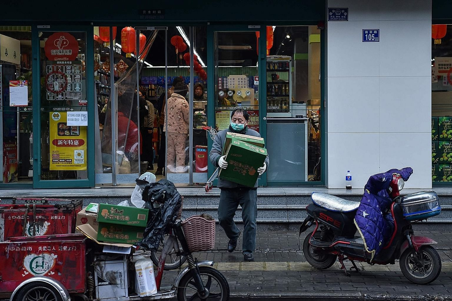 A man wearing a face mask at a market in Wuhan on Sunday. Nearly 40 million people have been under lockdown in and around Wuhan, the epicentre of the outbreak and the capital of Hubei province, just before the Chinese New Year holidays.