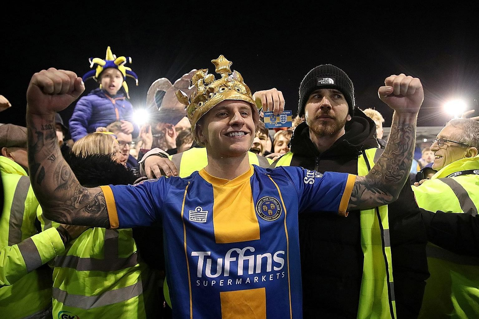 Left: Jason Cummings, Shrewsbury's two-goal hero, is crowned after the 2-2 draw in the FA Cup fourth round, as stewards prevent ecstatic fans from mobbing him. PHOTO: REUTERS Below: Curtis Jones putting runaway Premier League leaders Liverpool 1-0 up