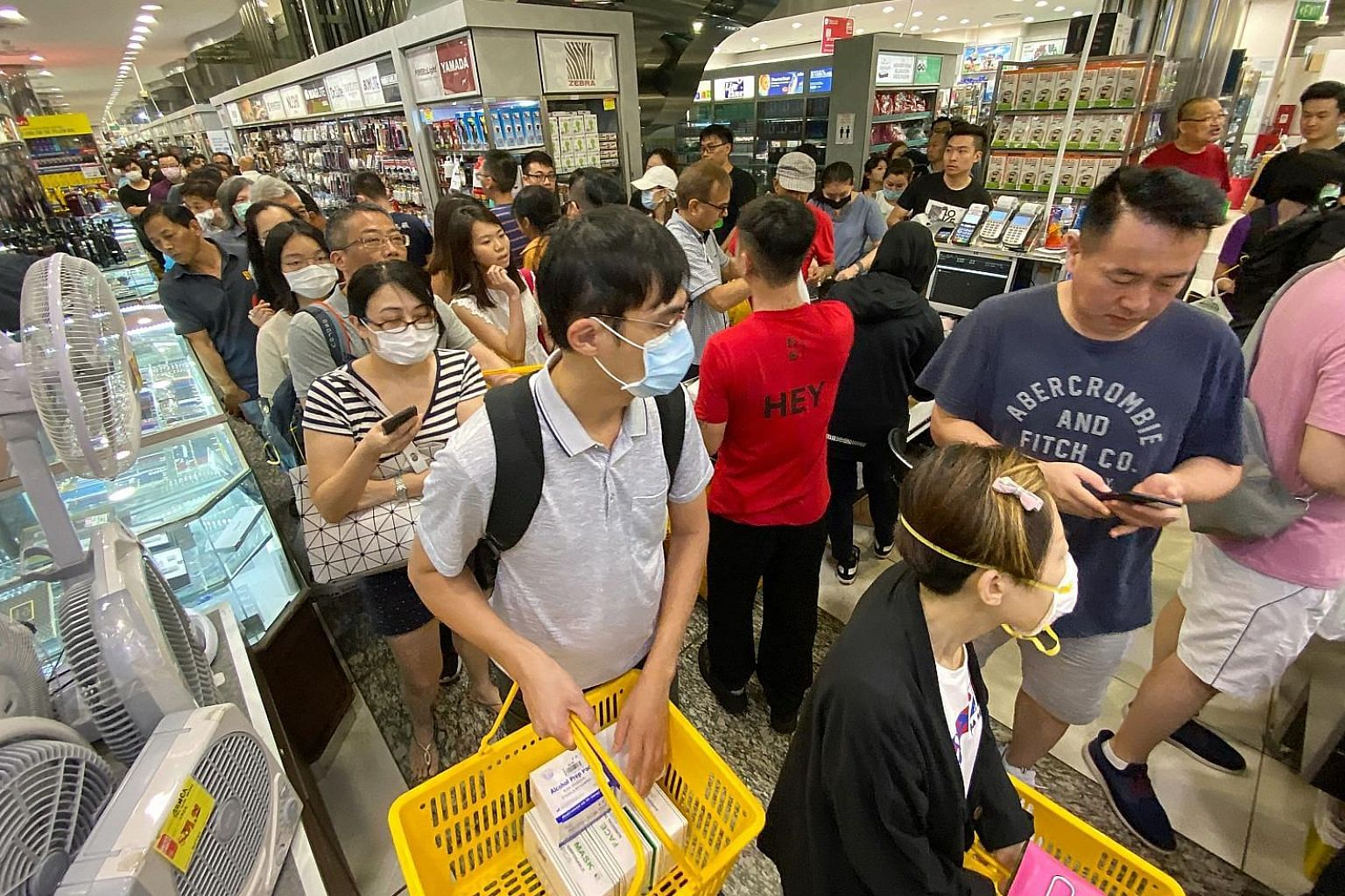 People queueing to buy boxes of masks at Mustafa Centre yesterday. Senior Minister of State for Health Lam Pin Min said there are enough masks if people use them sensibly.
