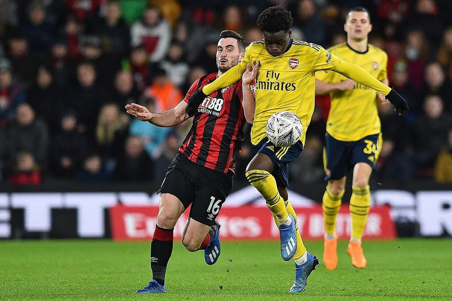Arsenal's Bukayo Saka holding off Bournemouth's Lewis Cook during their FA Cup tie on Monday. The Gunners won 2-1, with the youngster opening the scoring, to set up a fifth-round meeting with Portsmouth. PHOTO: AGENCE FRANCE-PRESSE