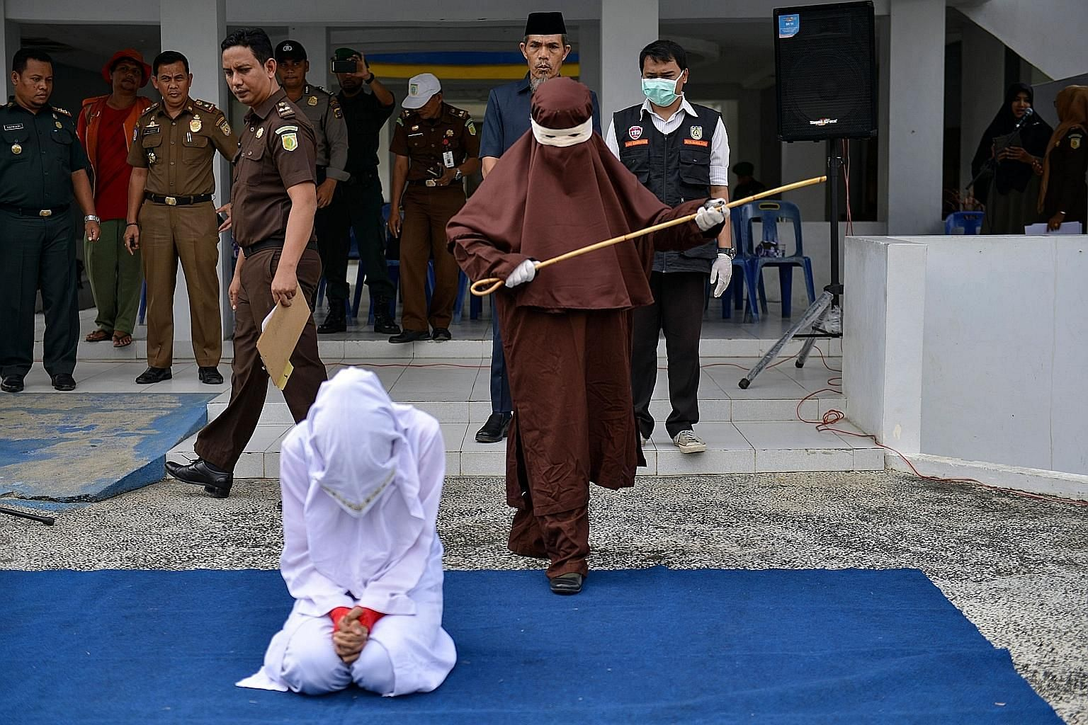 A member of the first female flogging squad in Indonesia's Aceh province preparing to whip a woman last month. Public whipping is a common punishment in the province for premarital sex, adultery, drinking alcohol, gambling and other behaviour that co