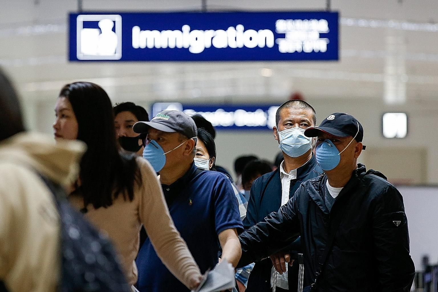 Passengers arriving from Guangzhou waiting in line at immigration at the Ninoy Aquino International Airport in Manila on Jan 22. The Philippines has cancelled direct flights to Wuhan and stopped issuing visas on arrival to Chinese nationals. Flights