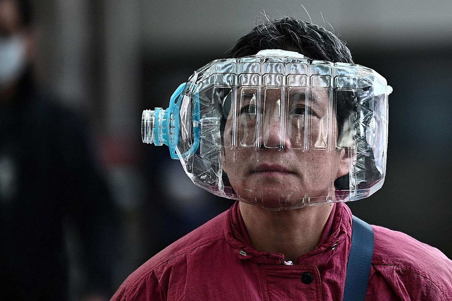 A pedestrian in Hong Kong uses a plastic water bottle with a cutout (above) for protection following the virus outbreak in Wuhan while a woman wears a mask in Shanghai.