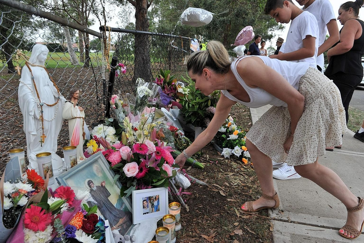 People gathering yesterday at a makeshift memorial at the site of an accident, which killed two sisters, their brother and a cousin, in the Oatlands suburb of Sydney. Three other children were seriously injured. A 29-year-old driver was charged with