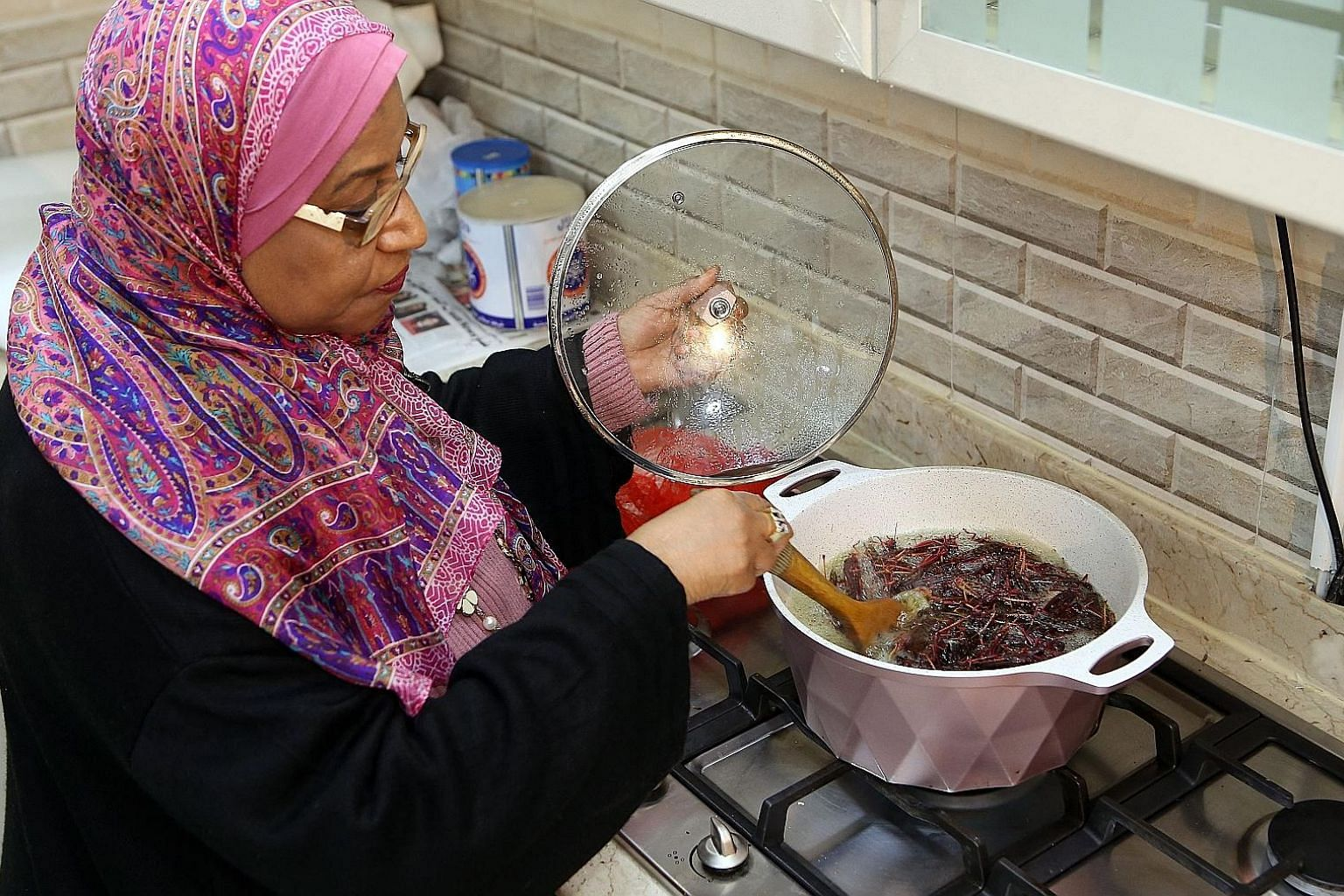 Ms Moudi Al-Miftah cooks a potful of locusts at her home in Al-Ahmadi. She puts them into boiling stock, where they turn red, filling her kitchen with an aroma similar to stewing mutton. A locust vendor in a market in Kuwait with a bag of edible inse