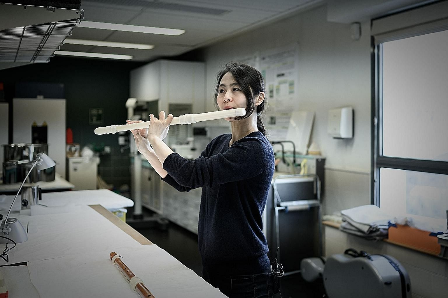 Musician Mina Jang plays the 3D-printed replica of a wooden transverse flute at the music lab of the Museum of Music in Paris.