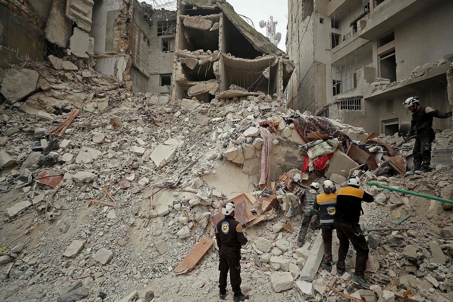 Rescue workers searching for victims amid the rubble of a building that was hit during an air strike by Syrian forces on the rebel-held town of Ariha in the northern countryside of Syria's Idlib province yesterday. Syria has pressed on with its offen