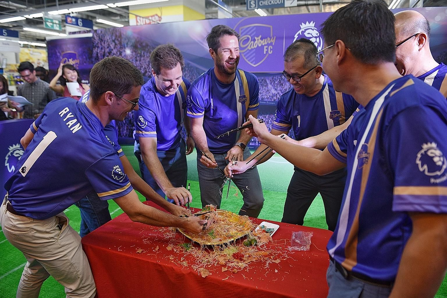Former England footballer Jamie Redknapp (centre), in Singapore during the Chinese New Year, tossing yusheng during the traditional lohei session at a Cadbury event yesterday. ST PHOTO: KELLY HUI