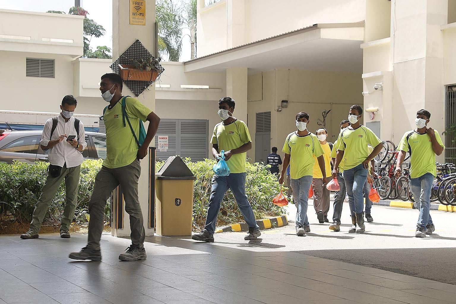 Workers staying at The Leo dormitory in Kaki Bukit were seen wearing masks yesterday. A Bangladeshi worker infected with the virus was said to have been housed there. The Ministry of Manpower said the worker had spent time only in his dorm room and a