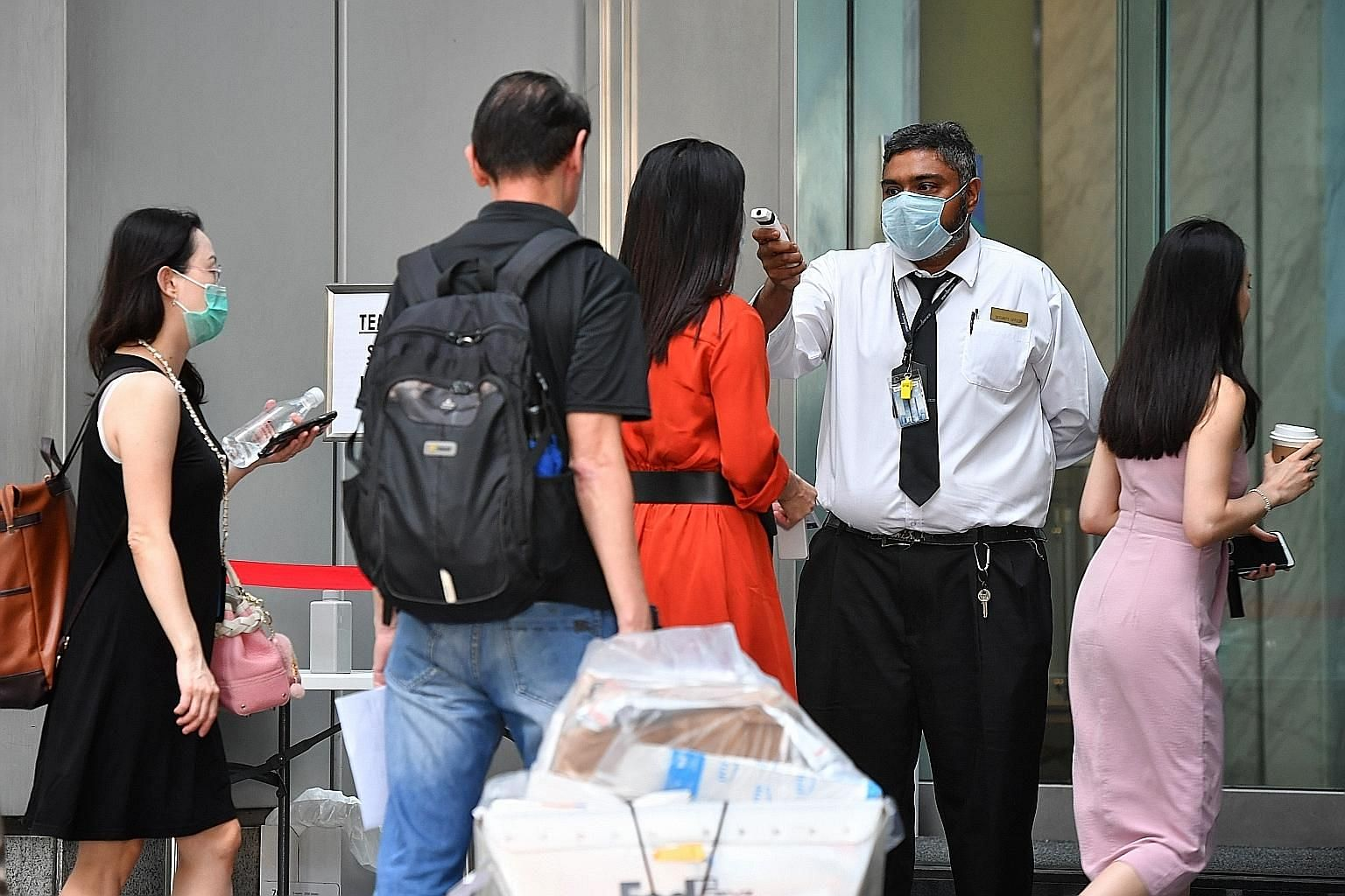 People queueing to get their temperatures taken at One Raffles Place yesterday. Snaking queues were seen at places like Raffles Place and Suntec City as temperature checks and visitor screening were carried out.
