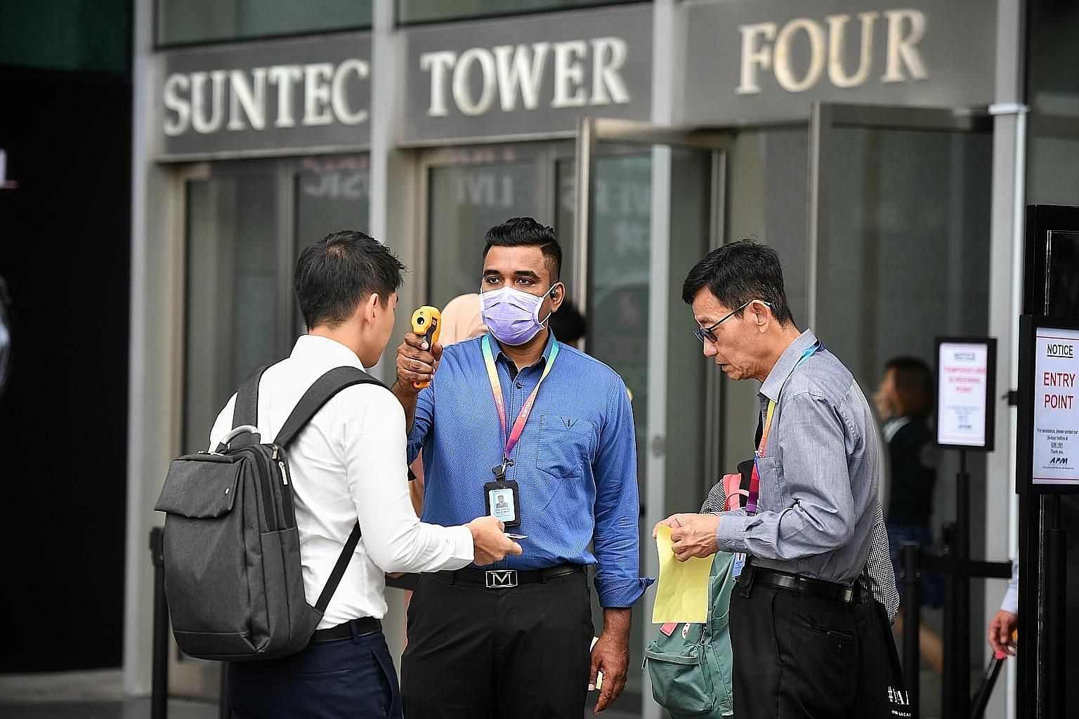An employee getting his temperature checked before entering Suntec City yesterday. Some firms have also cancelled large-scale internal meetings such as training sessions, seminars and workshops. ST PHOTO: CHONG JUN LIANG