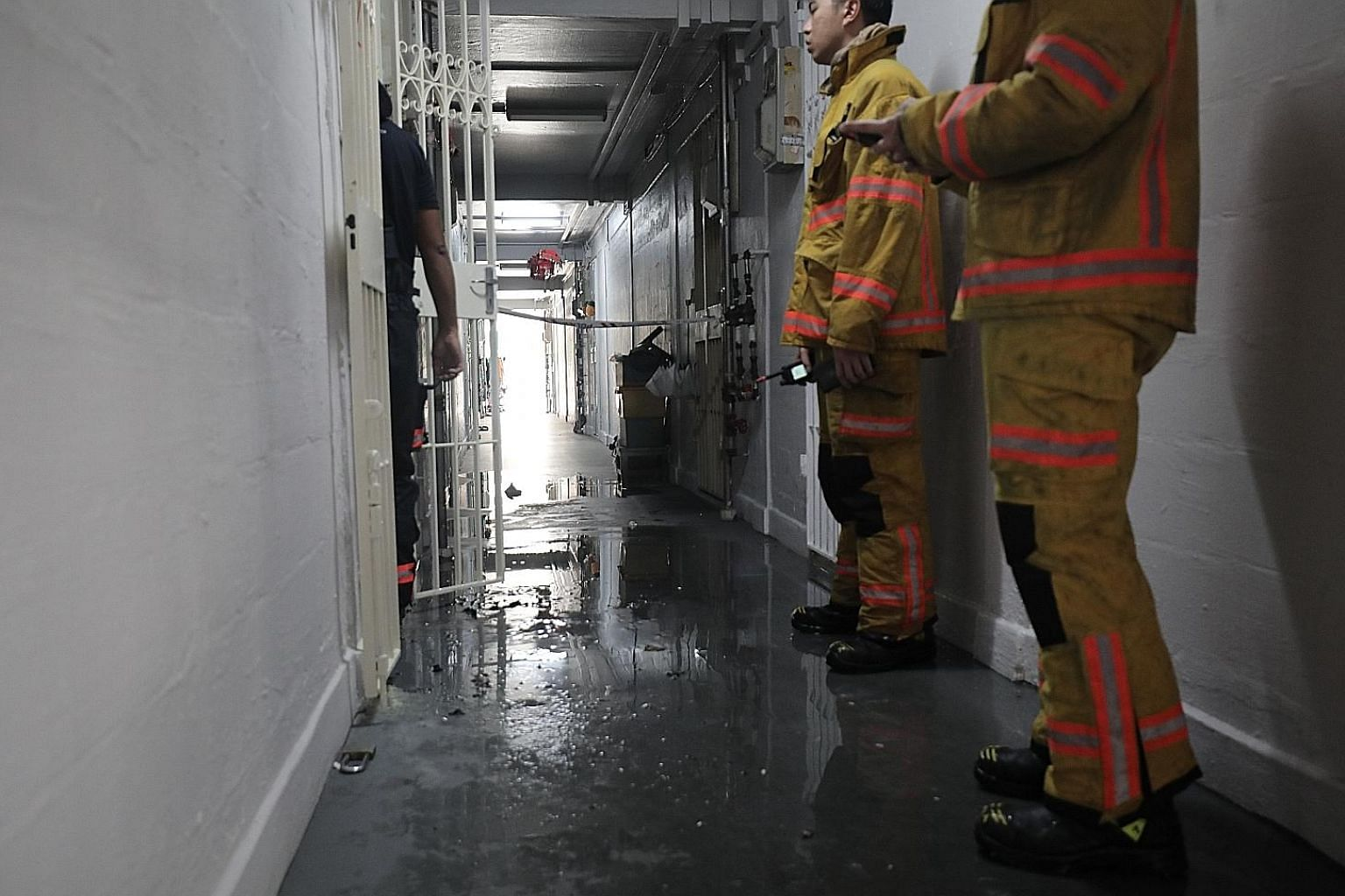 SCDF officers at the Ang Mo Kio flat yesterday. The man was found in the living room with burn injuries and taken to Tan Tock Seng Hospital, where he later died. PHOTO: LIANHE ZAOBAO