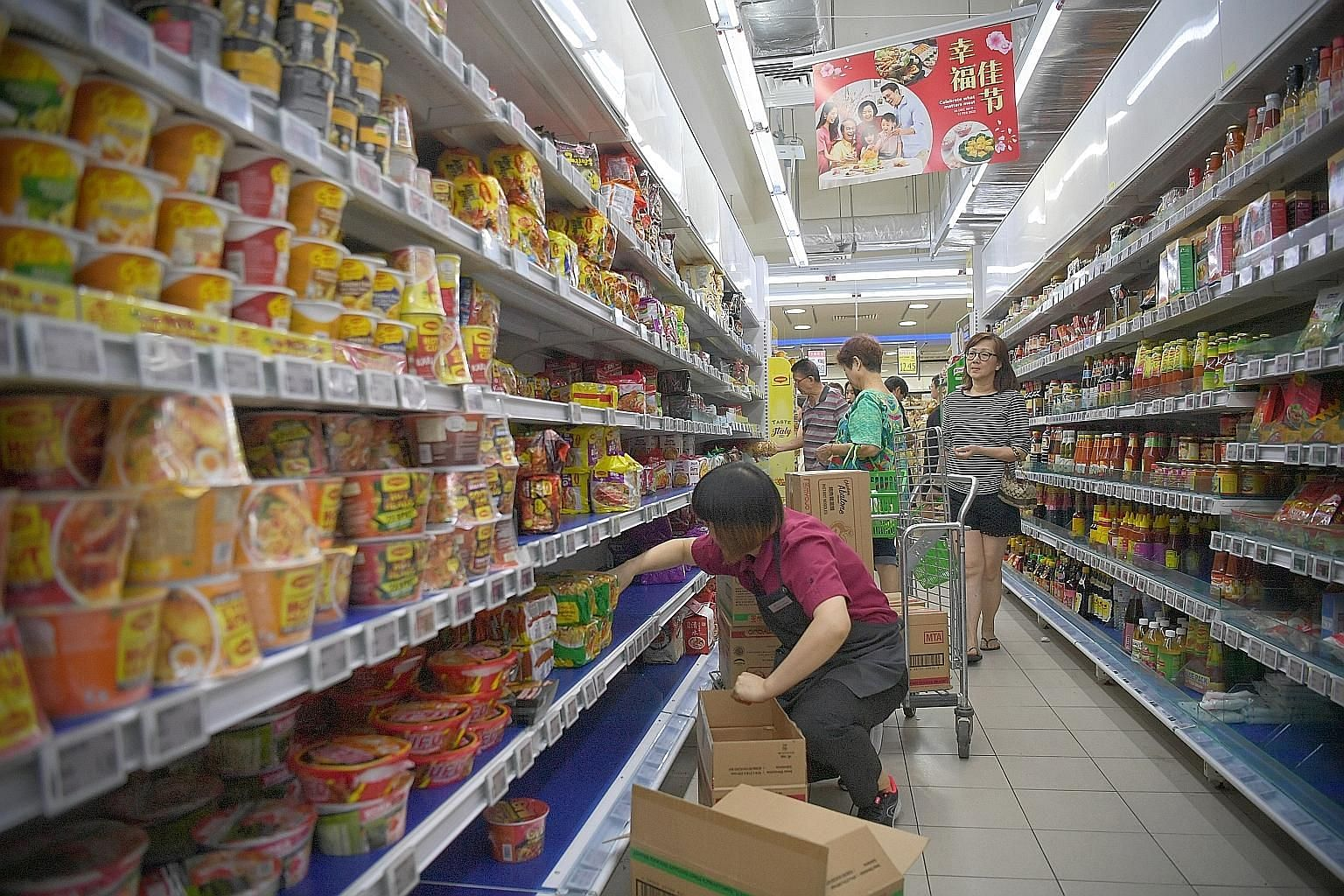 Shelves of daily essentials as well as instant noodles being refilled at a FairPrice outlet at Block 212 Bedok North Street 1.Price Finest outlet in Paya Lebar (above) walking past empty shelves last Saturday.