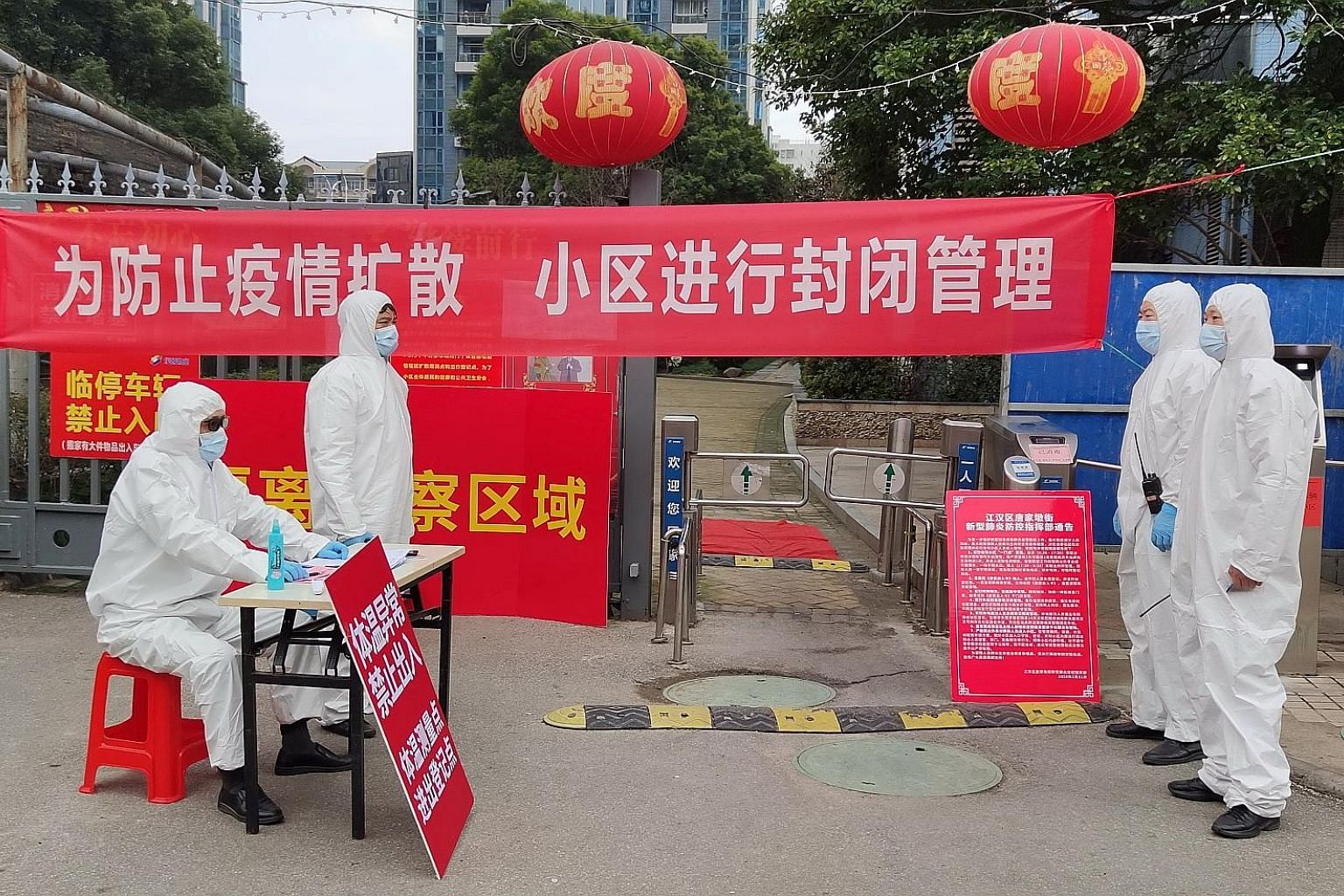 Workers manning a checkpoint where visitors have to register and get their temperature taken at an entrance to a residential compound in Wuhan, Hubei province, on Thursday.