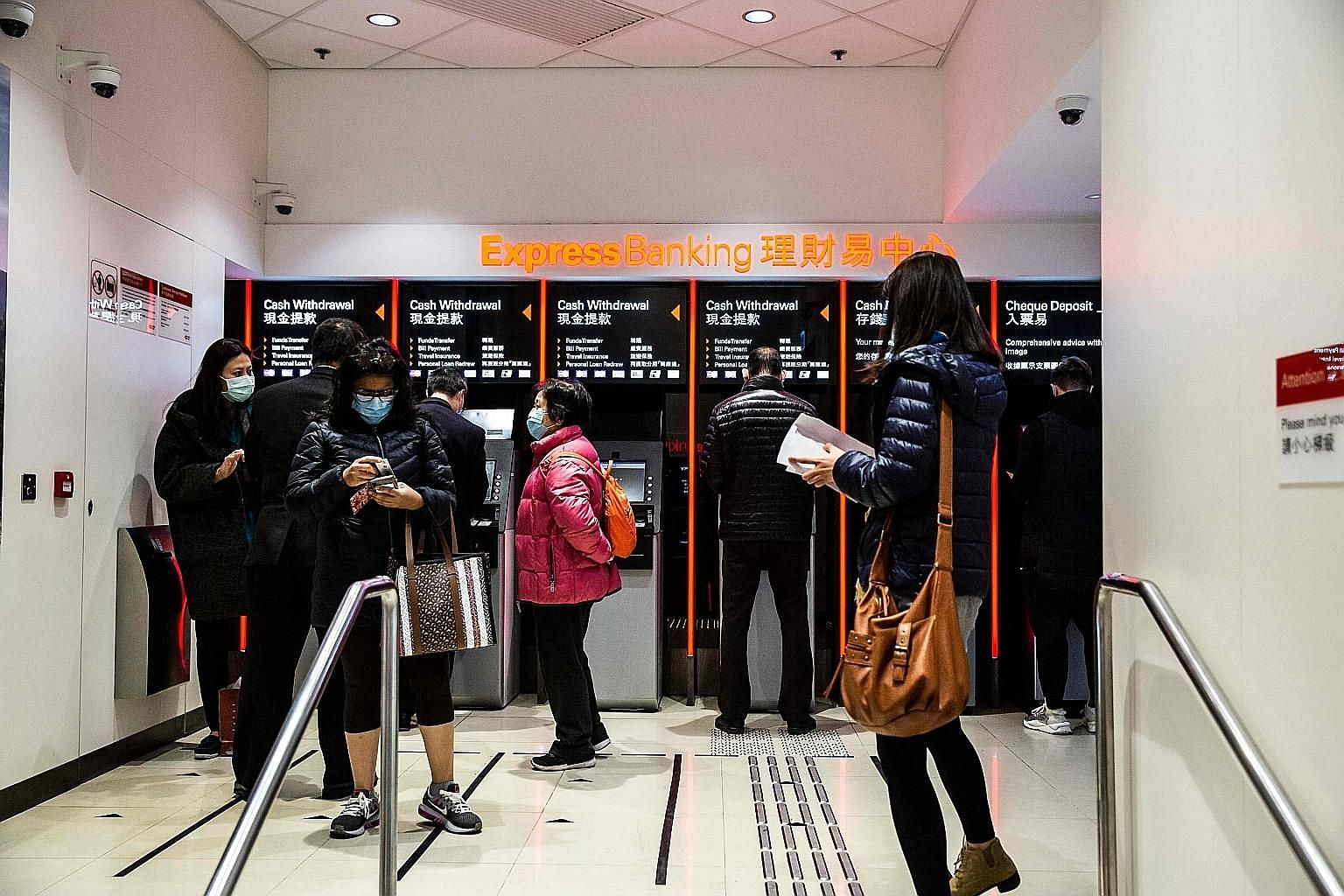 Customers using the express banking services inside an HSBC branch in Hong Kong yesterday. The bank says it would merge its private banking and wealth businesses, axe European stock trading and cut US retail branches. HSBC will, instead, accelerate i