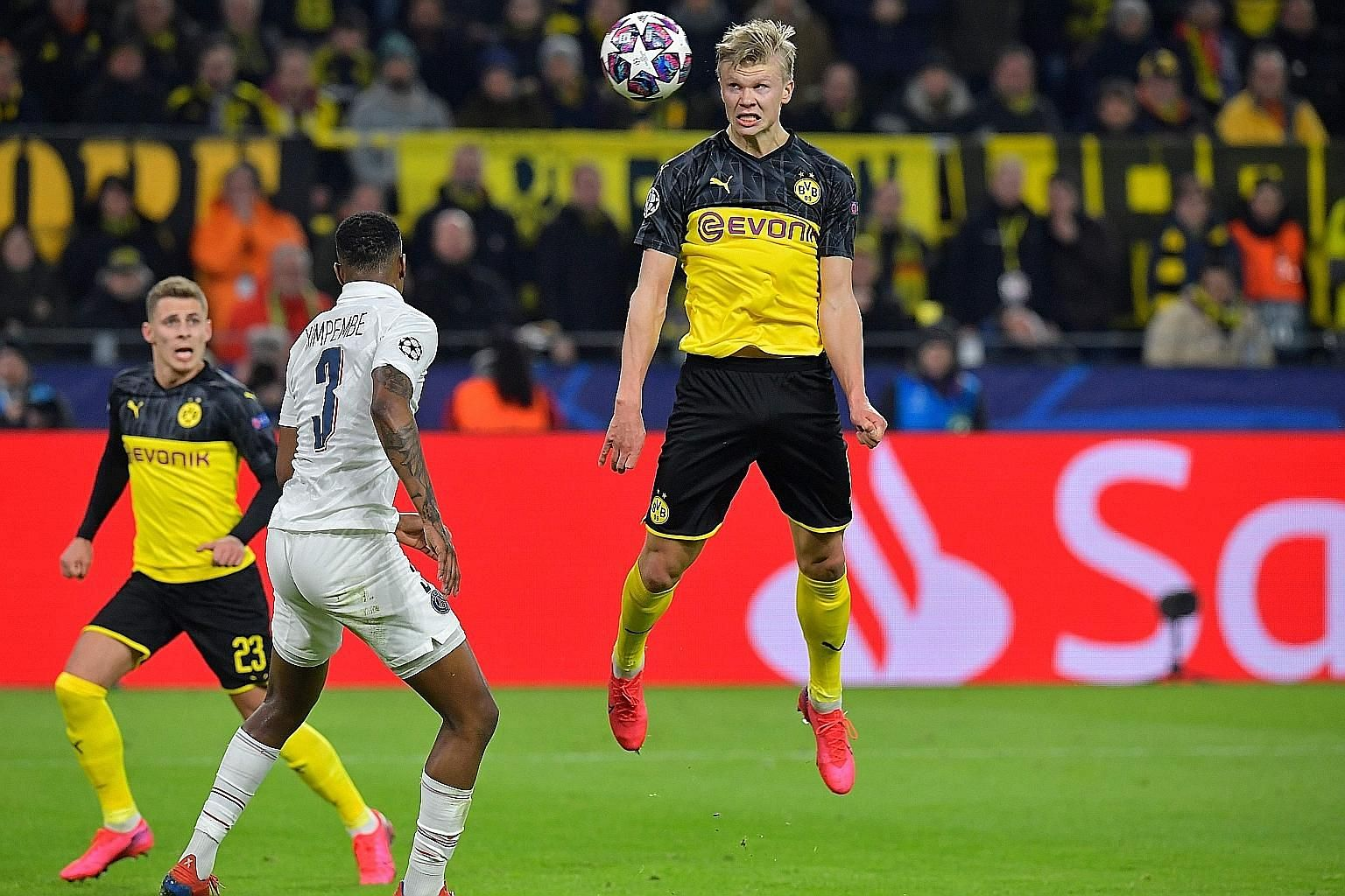 Borussia Dortmund's forward Erling Braut Haaland (centre) heading the ball next to Paris Saint-Germain's French defender Presnel Kimpembe during the first leg of their Champions League last-16 tie in Germany on Tuesday. PHOTO: AGENCE FRANCE-PRESSE