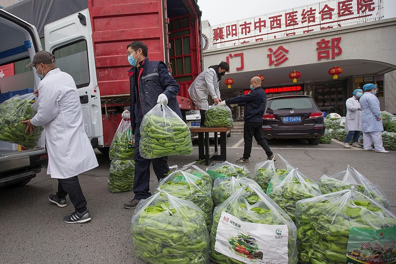 Medical workers receiving chillies donated from Shandong province at a hospital in the city of Xiangyang, in Hubei province, yesterday. Hubei has rolled out a slew of stricter measures this week, including lockdowns in communities and a ban on all mo