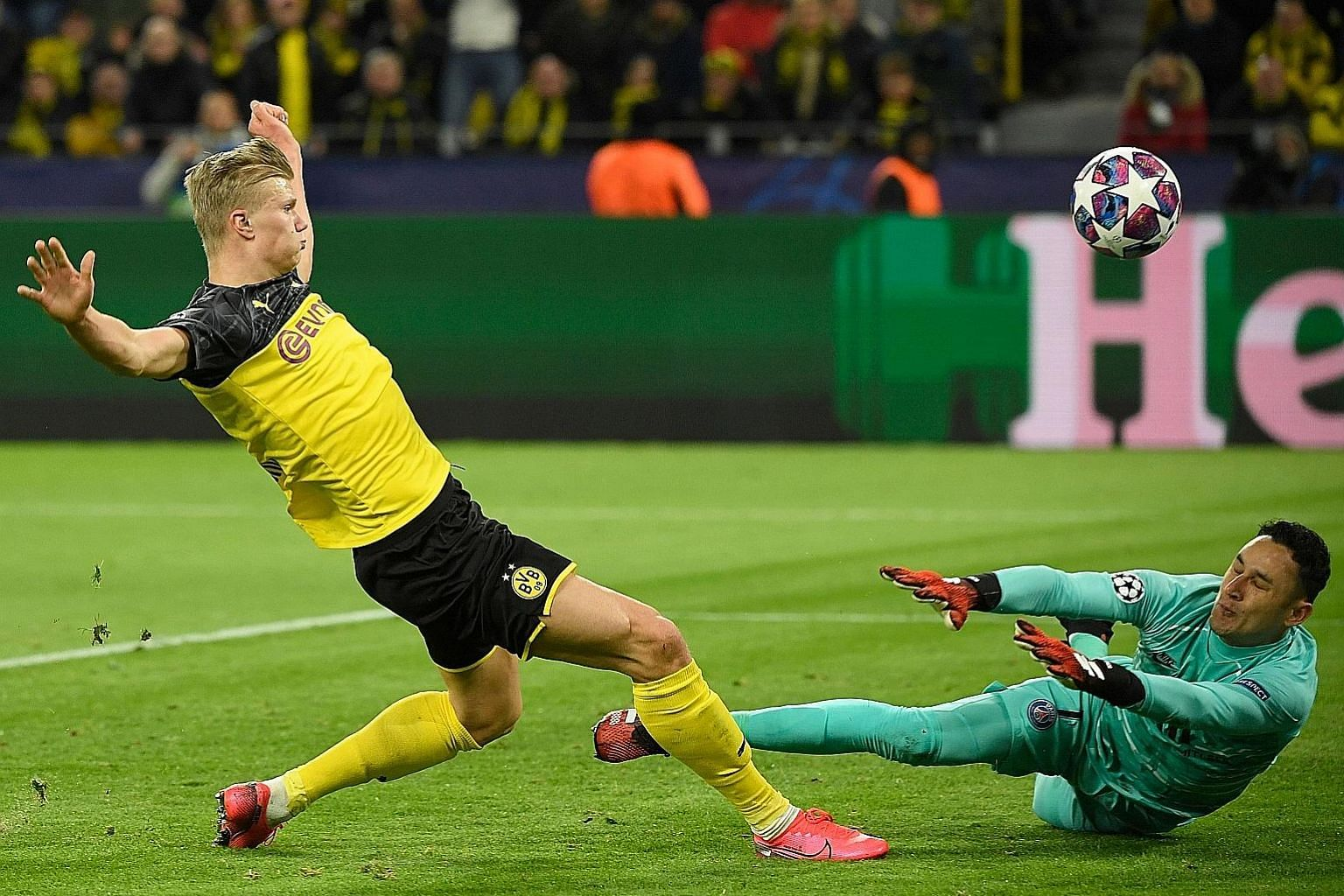 Erling Braut Haaland lifting the ball over PSG goalkeeper Keylor Navas to score the first goal. Dortmund have the edge in the tie after the Norwegian teenager's two goals. PHOTO: AGENCE FRANCE-PRESSE