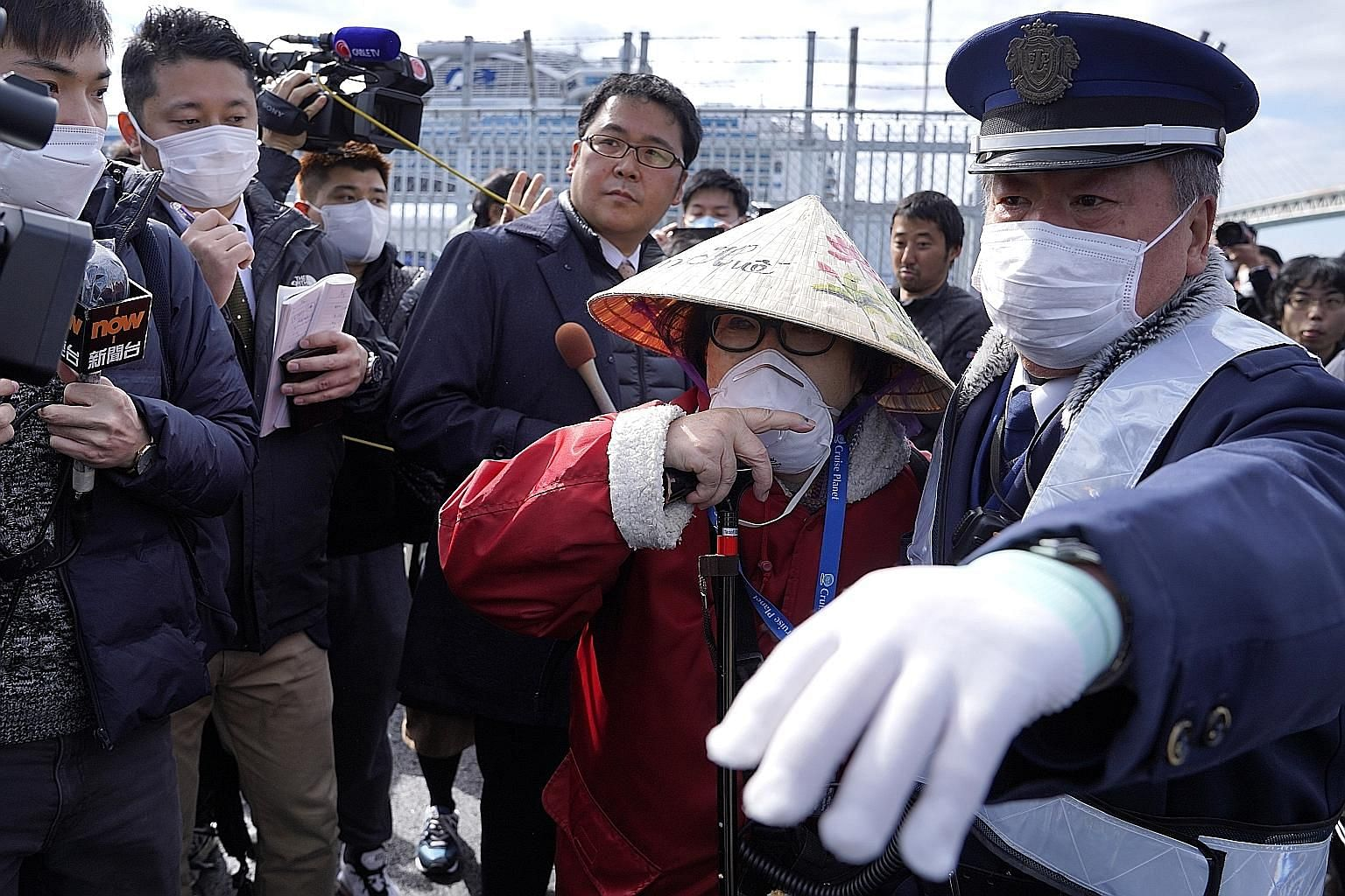A passenger from the Diamond Princess cruise ship surrounded by members of the media as she left the Daikoku Pier Cruise Terminal in Yokohama yesterday. The first batch of 443 passengers, out of the 3,000 or so still on board, were allowed to leave t