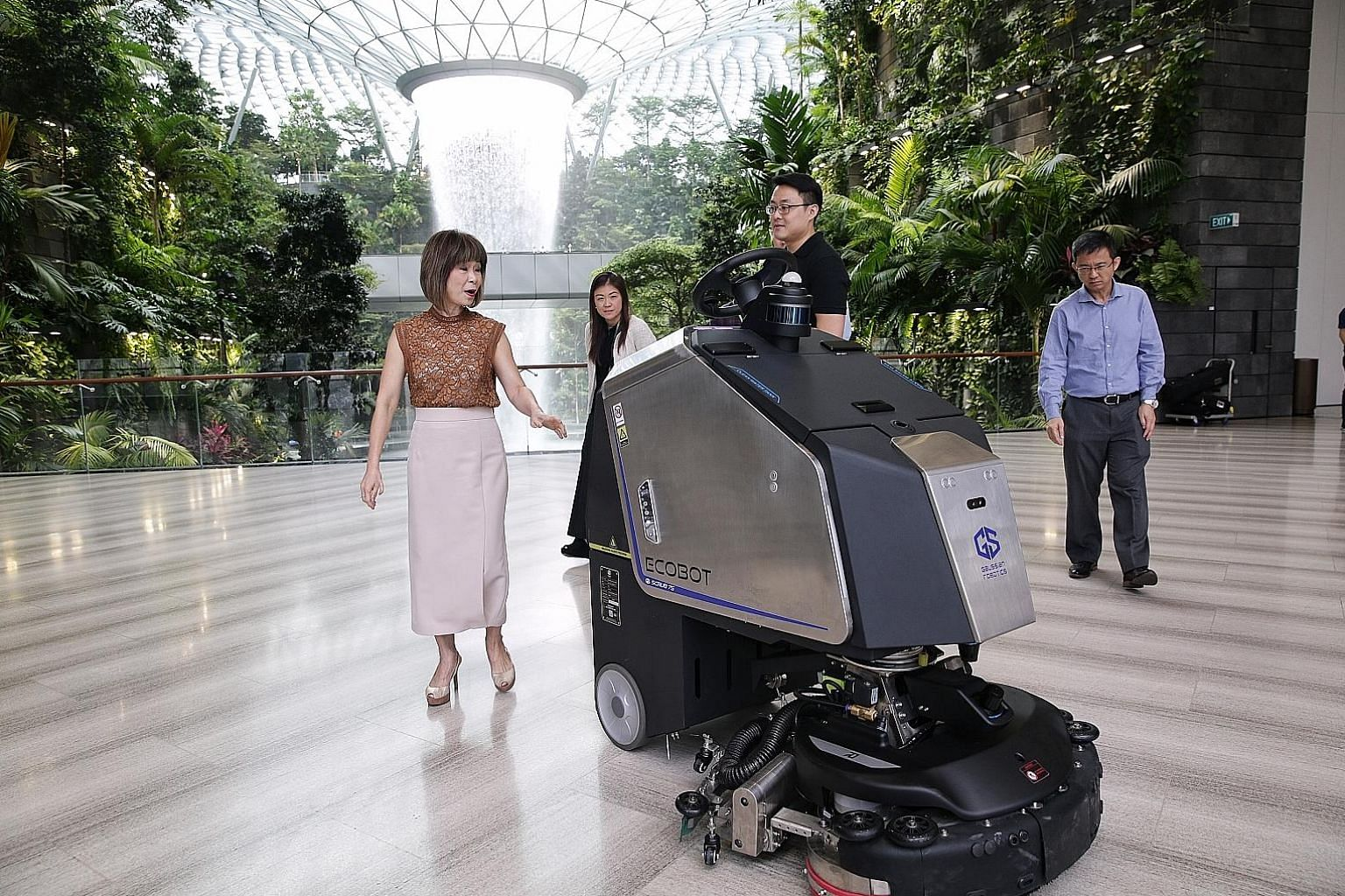 Senior Minister of State for the Environment and Water Resources Amy Khor (far left) being shown an Ecobot autonomous scrubber at work by Gaussian Robotics' head of business development Kevin Lee (in black) yesterday. With them were Jewel Changi Airp