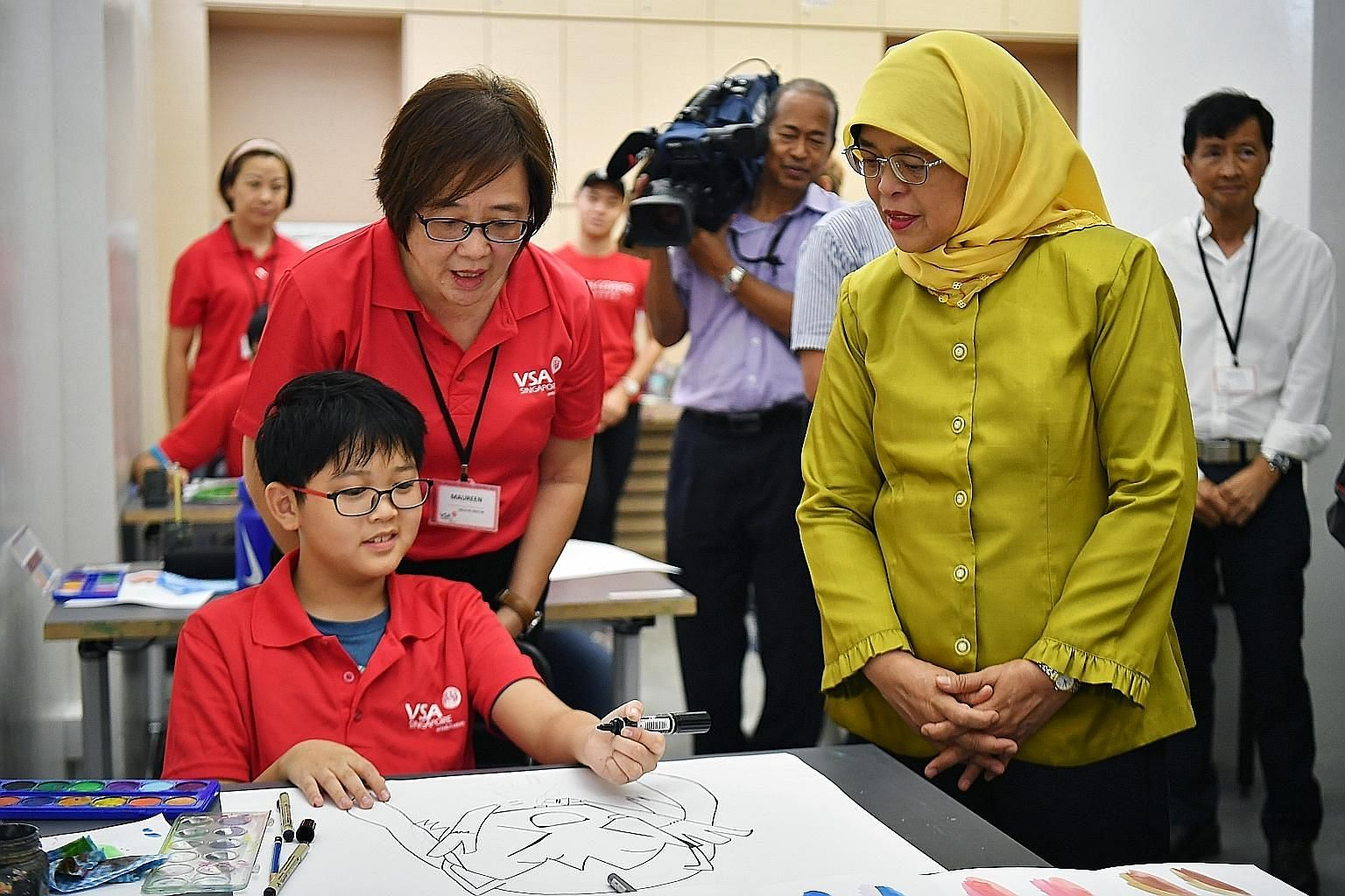 President Halimah Yacob and VSA Singapore executive director Maureen Goh observing student Royce Tai, 13, working on his drawing in VSA Artspace @ Bedok yesterday. Her visit was part of the President's Challenge outreach efforts to help vulnerable gr