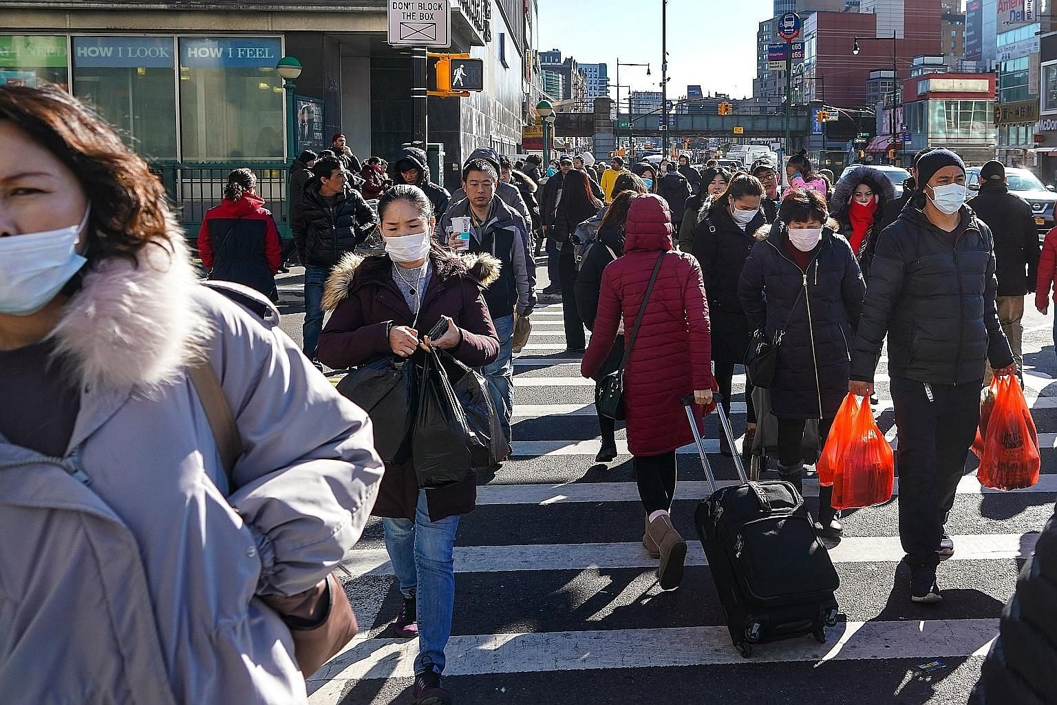 Pedestrians in the Chinatown area of Queens, New York. The US Centres for Disease Control and Prevention is gearing up for the community spread of the coronavirus in the US, warning it is not a matter of if, but when and how many people in the countr