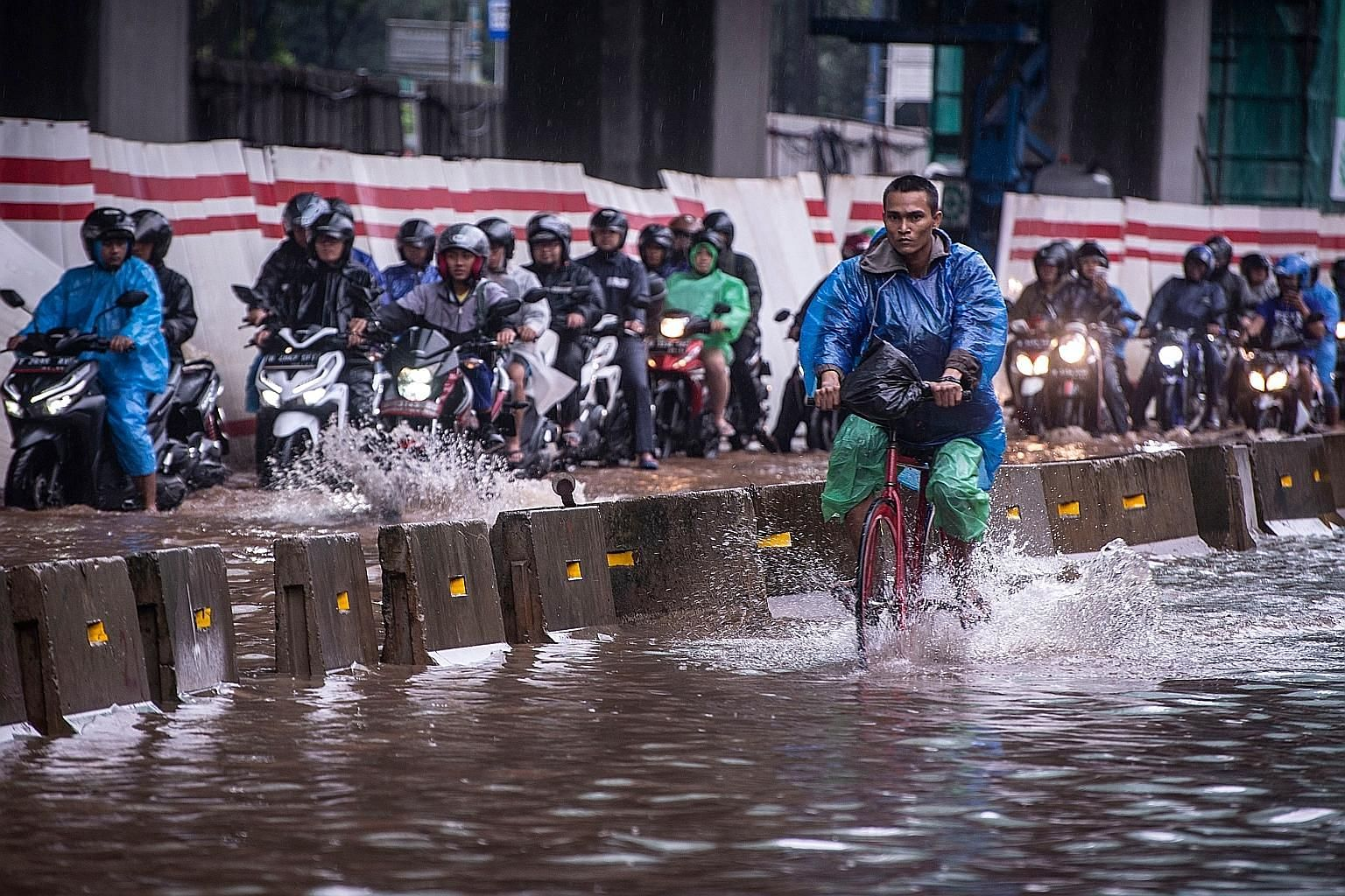 A flooded street in Jakarta, Indonesia, on Tuesday. The country is already planning to move its capital to the island of Borneo, as Jakarta is slowly sinking and suffers from regular flooding. Compared with China and Japan, Indonesia has limited reso