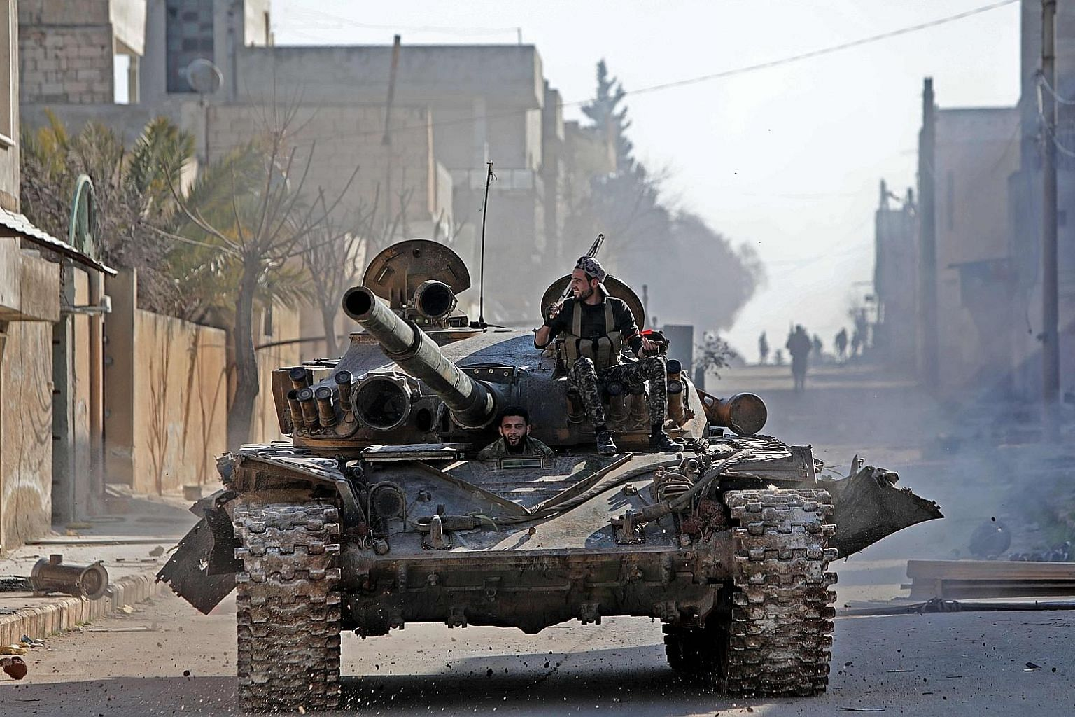 Turkey-backed Syrian fighters riding in a tank on Thursday in the town of Saraqib, in the eastern part of Syria's Idlib province.