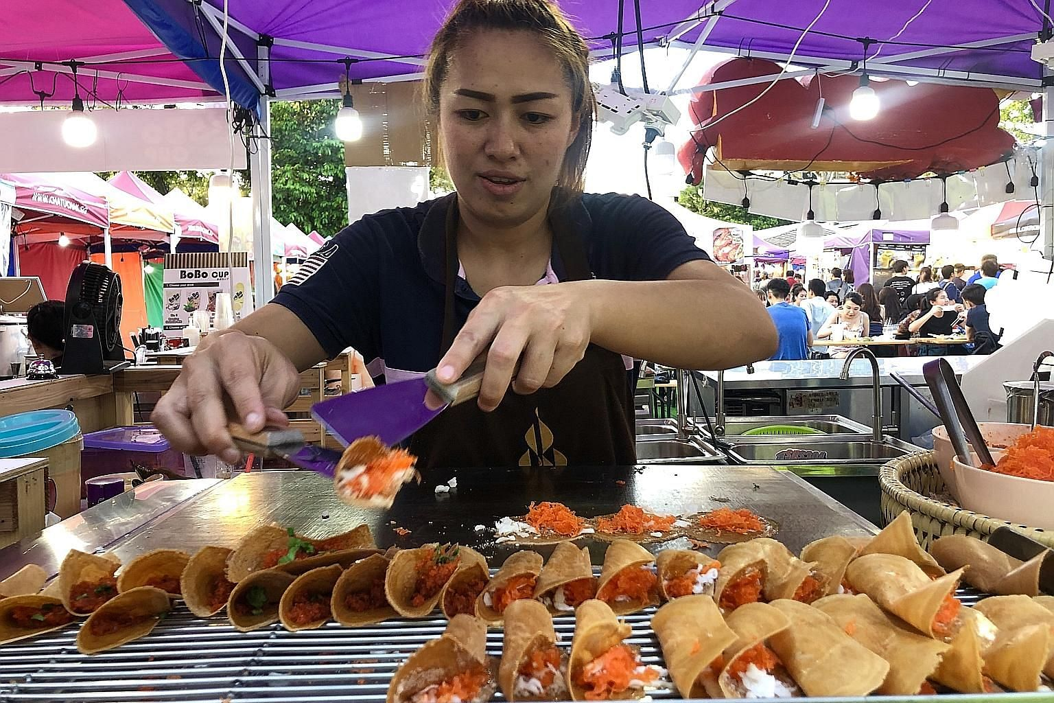 Ms Kik Pornpimon, 29, flew in from Bangkok to make and sell Thai crispy pancakes at Chatuchak Night Market Singapore, which kicked off on Feb 4 and is open until May 3. The night market features 200 stalls, half of which sell food and drinks.