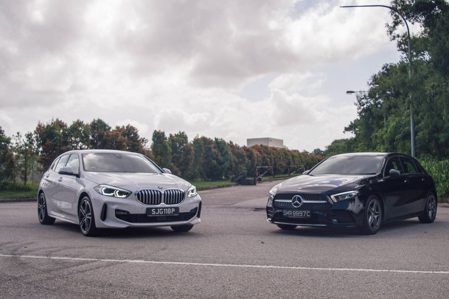 The BMW 118i M Sport (left) has high-gloss black exterior trims and 18-inch M wheels, while the Mercedes-Benz A200 AMG (right) sports a single-louvred diamond grille and 18-inch AMG wheels.