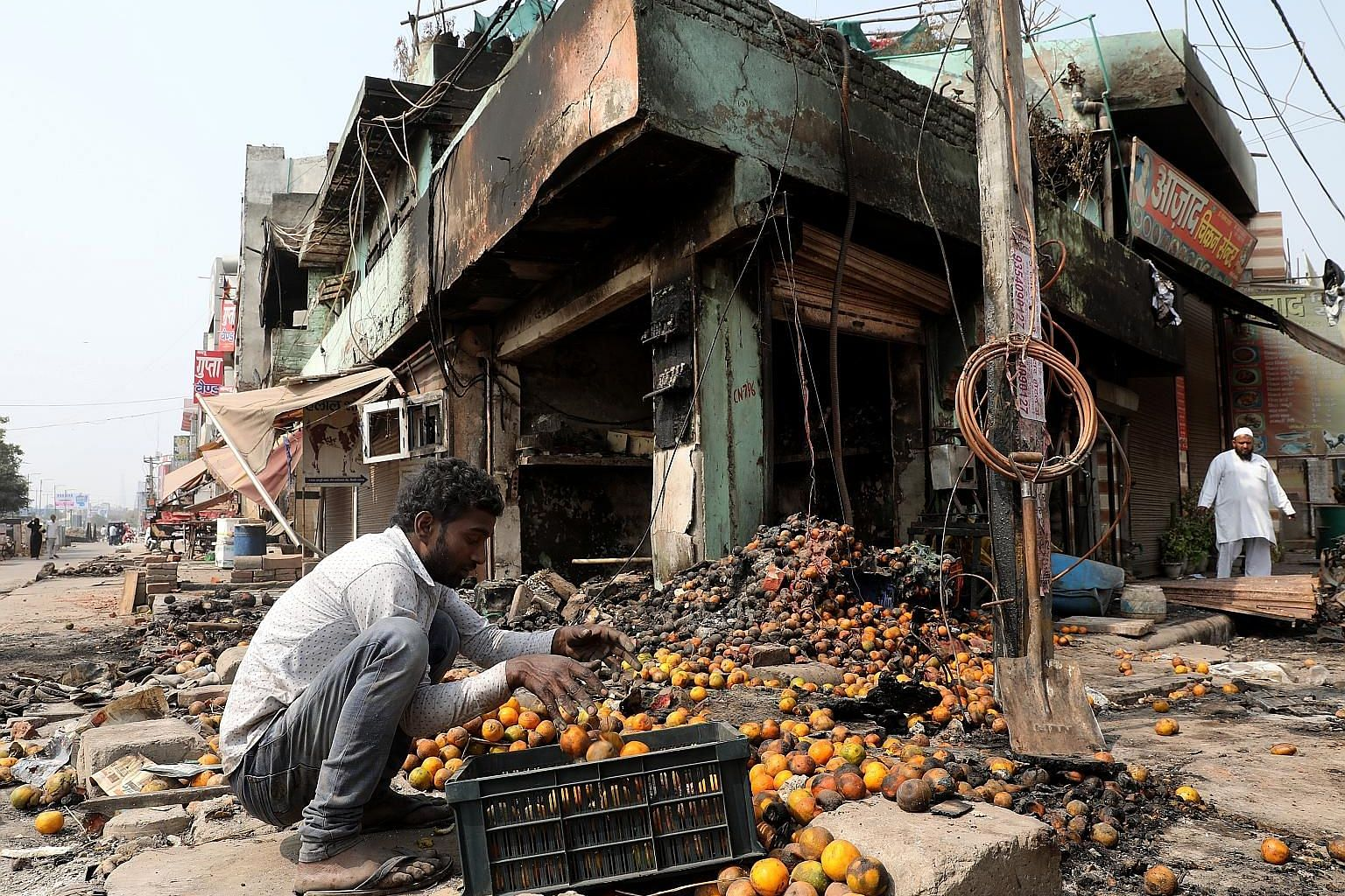 A family sitting amid the ruins of their home, which was set on fire by a mob during the riots. PHOTO: REUTERS A man collecting damaged fruits from a burnt-out area after the Hindu-Muslim riots in New Delhi last week. The riots broke out following cl