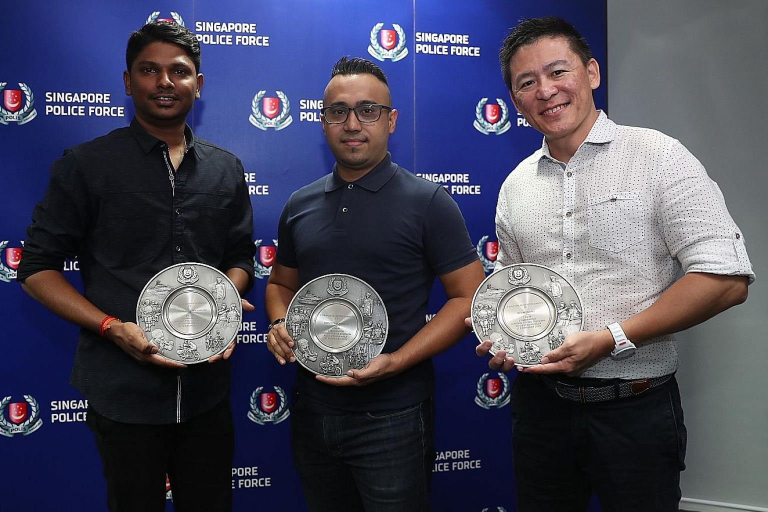 (From far left) Security officer Logaisraja Nadurajah, Certis auxiliary police officer Hidayat Hassan and Grab liaison officer Desmond Ng with their Public Spiritedness awards at Jurong Police Division last week.