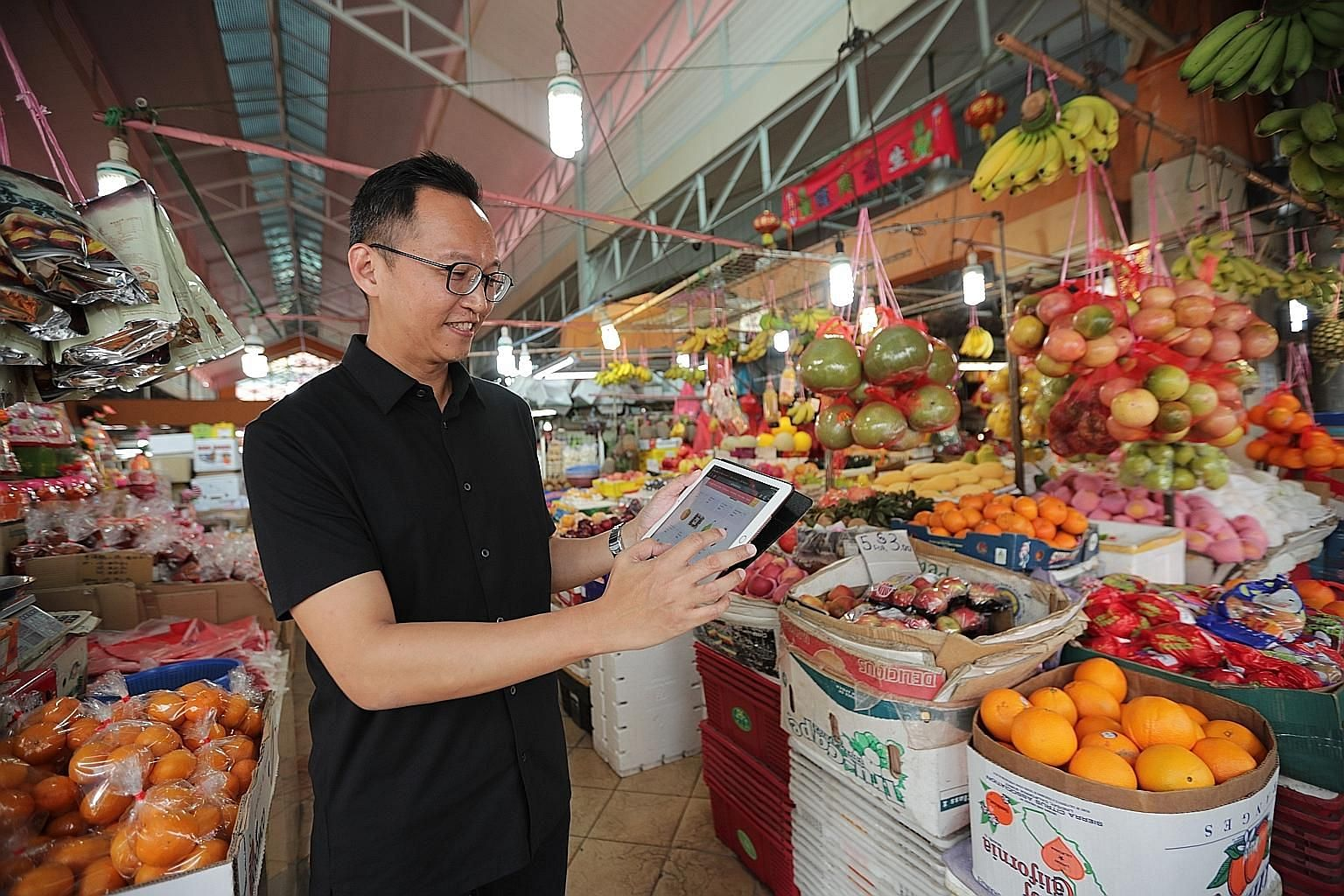 Mr Jon Lee of Chong Pang City Merchant and Hawker's Association browsing on the e-marketplace at Chong Pang market. Launched last June, the platform now has 29 retailers across trades such as selling fruit and vegetables.