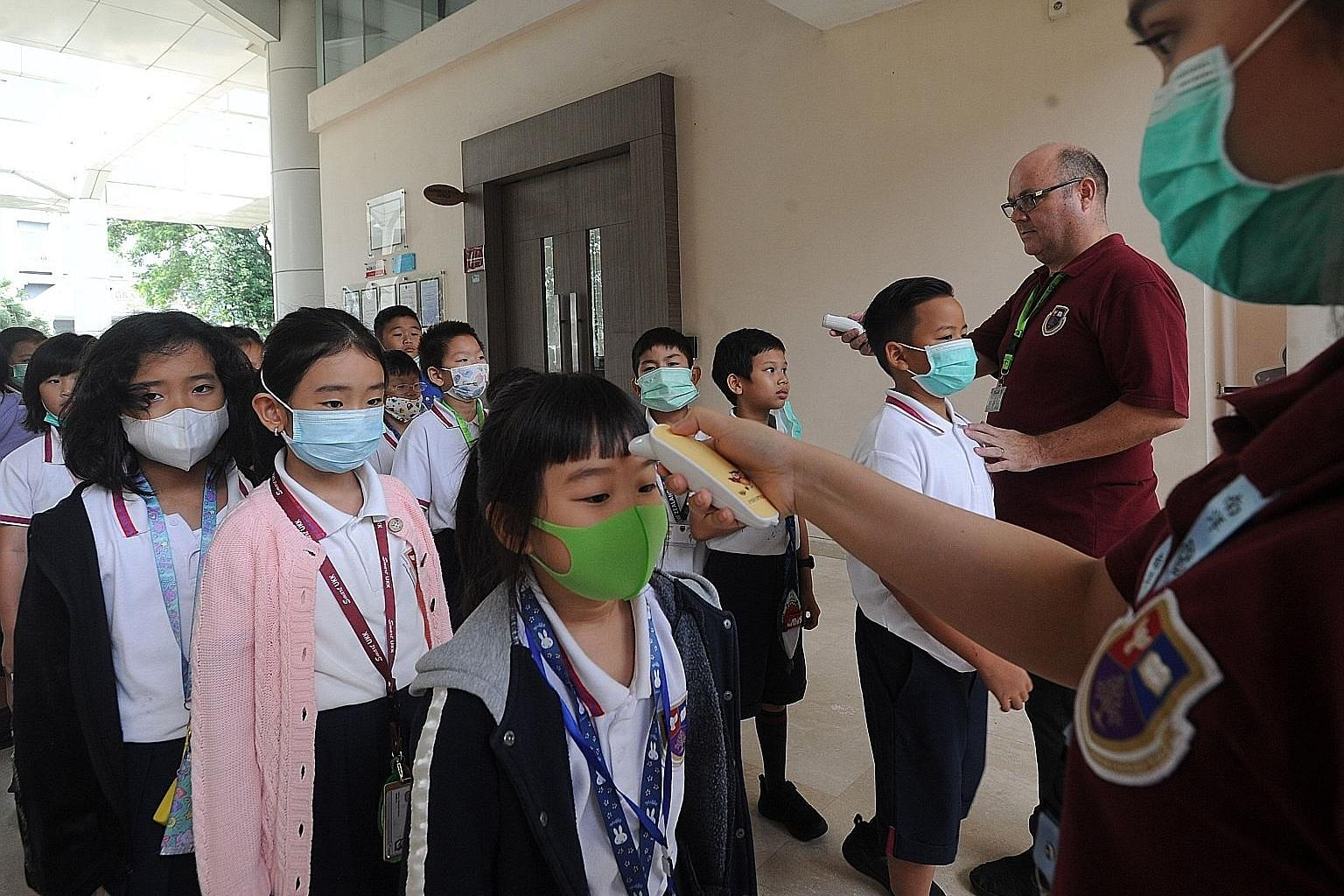 School officials checking the temperature of students before they entered a school in Tangerang, Indonesia, yesterday. PHOTO: AGENCE FRANCE-PRESSE
