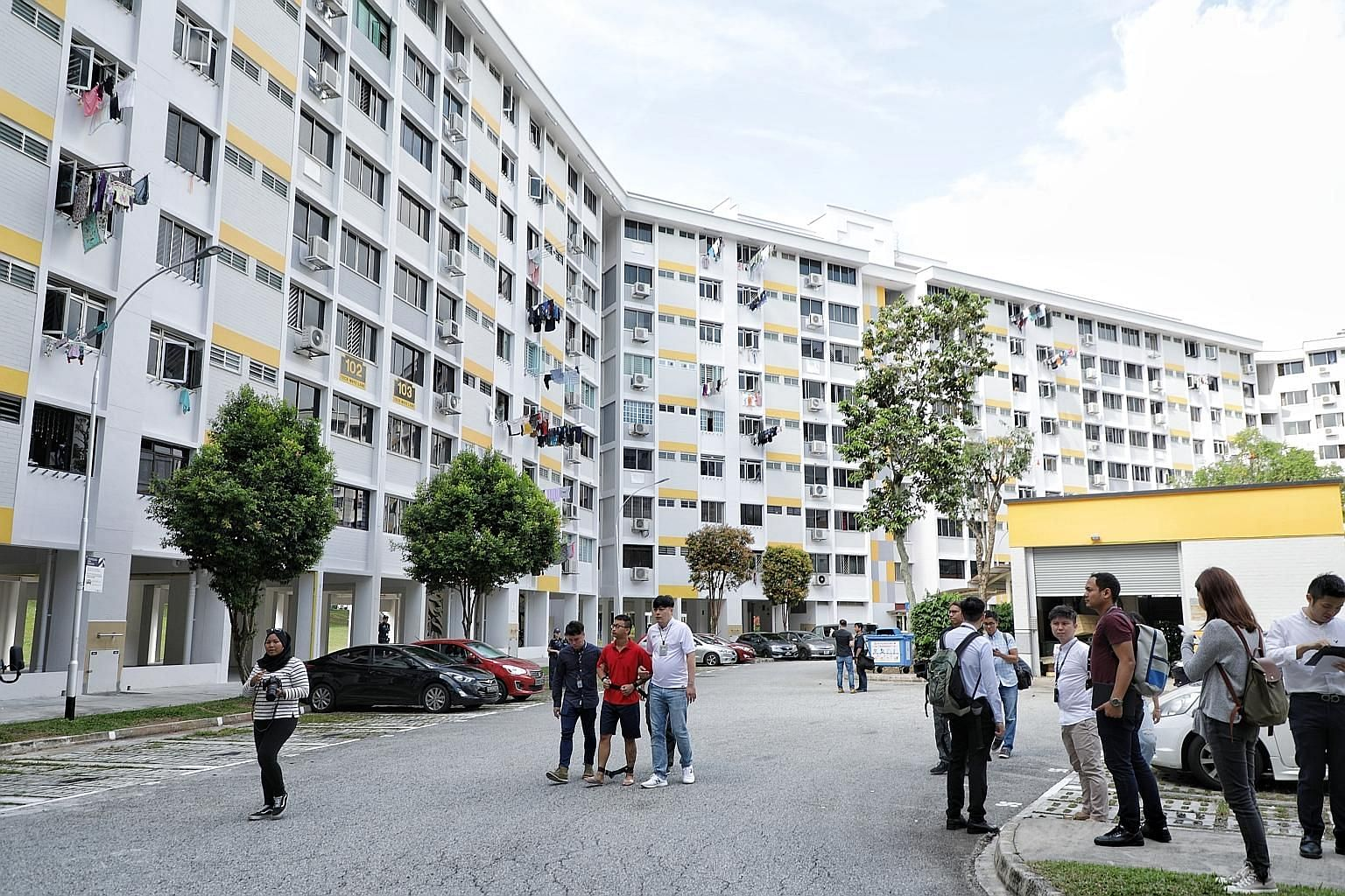 Police investigators near Block 102 Teck Whye Lane yesterday with one of the men accused of rioting at a void deck last Thursday.