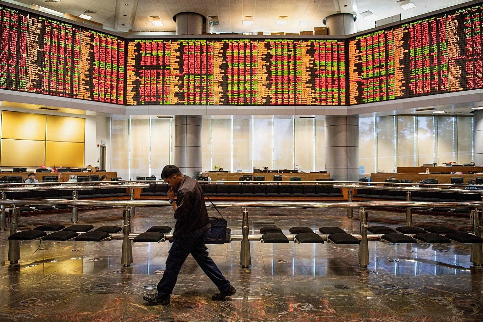 Electronic boards showing stock movements in Kuala Lumpur on Feb 24. Large corporate mergers and the award of contracts and licences are now in limbo following the change of government last week.