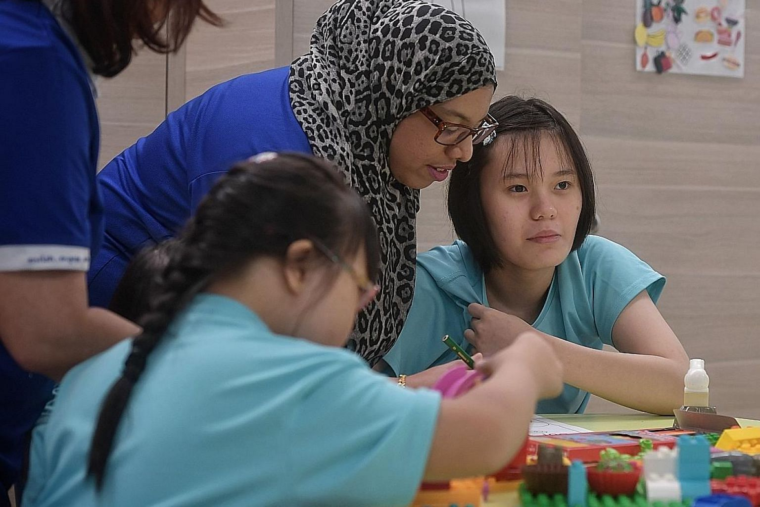 Kylie Tan (at right), 17, attends a special student care centre run by Minds. With the higher subsidy, her mother needs to pay only $35 a month, instead of $106, for her fees.