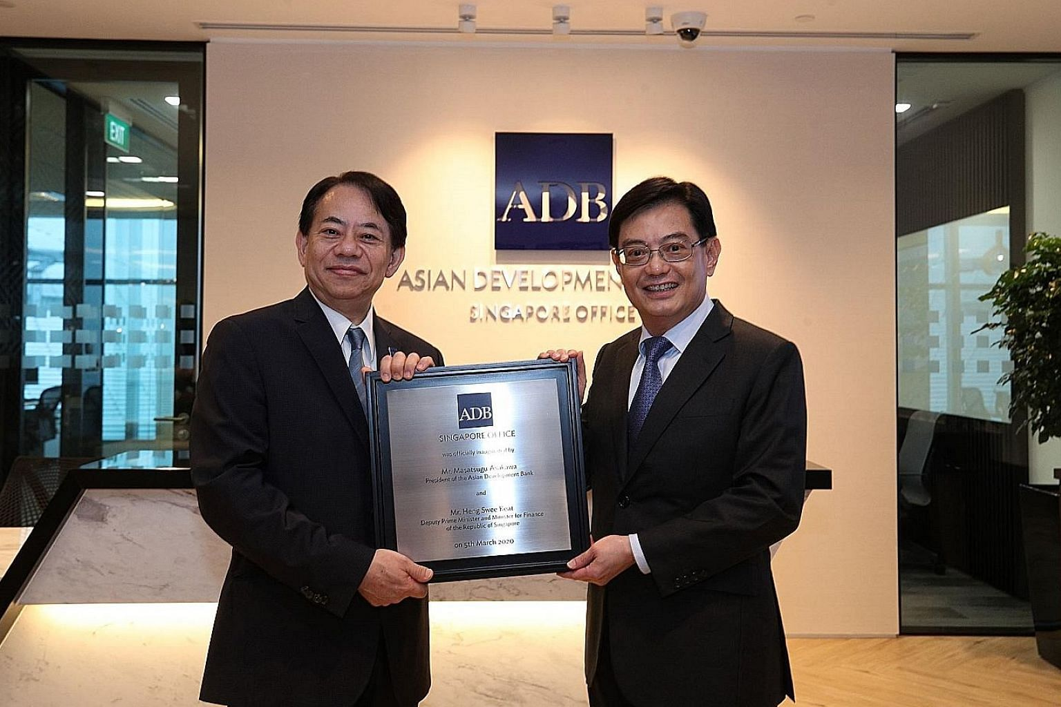 Asian Development Bank (ADB) president Masatsugu Asakawa (at left) and Deputy Prime Minister and Finance Minister Heng Swee Keat holding a plaque marking the official opening of the bank's new office in Marina Bay Financial Centre Tower 3 yesterday.
